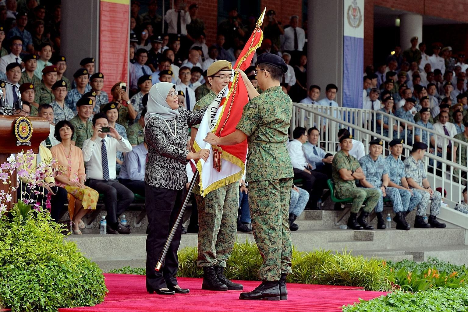 Colonel Paul Cheak, Chief Army Intelligence Officer, receiving the new Regimental Colours from President Halimah Yacob on behalf of the Headquarters Army Intelligence, as the Singapore Armed Forces (SAF) commemorated SAF Day at the Safti Military Ins