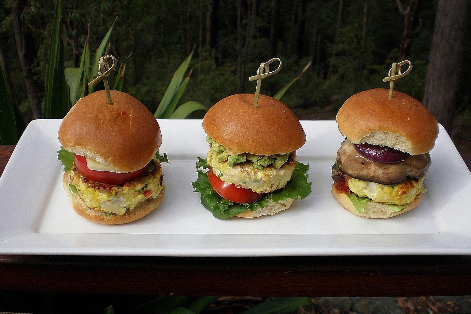 Spicy chicken sliders with (from left) cheese, tomato, sweet chilli sauce and coriander; mashed avocado, tomato and lettuce; and red onion, sauteed mushroom, chutney and lettuce.