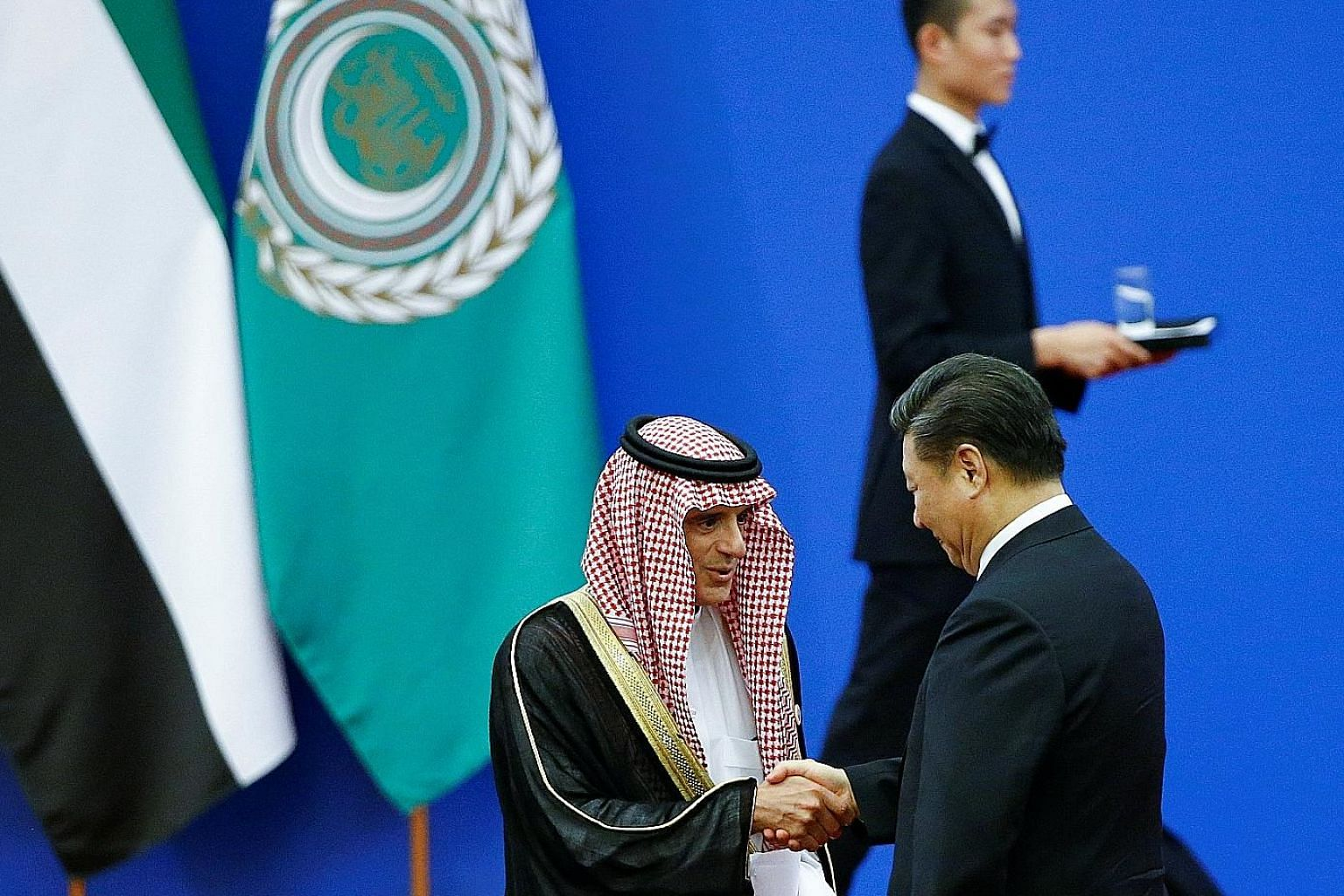 Chinese President Xi Jinping greeting Saudi Arabia's Foreign Minister Adel bin Ahmed Al-Jubeir at a China-Arab forum in Beijing yesterday.