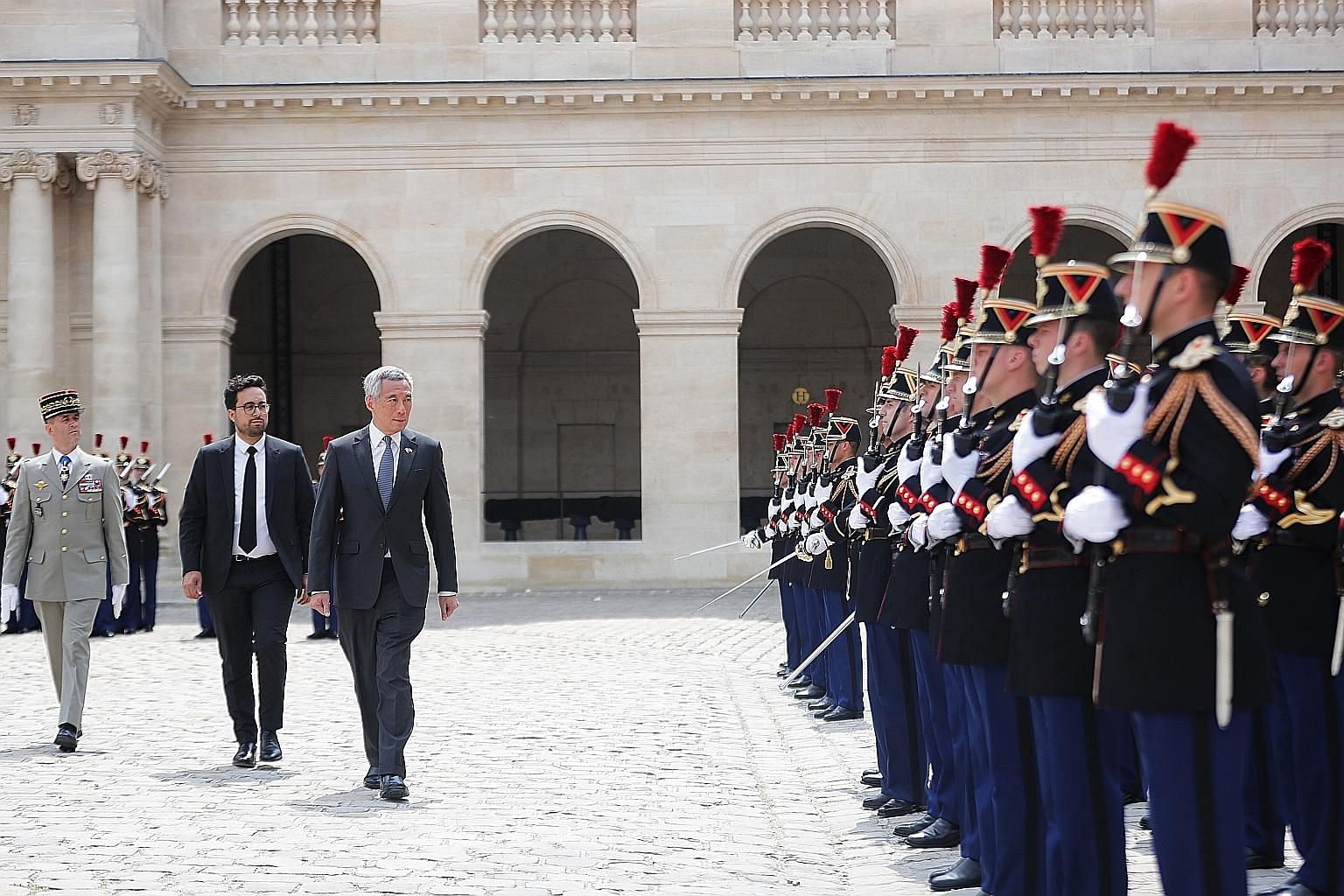 Prime Minister Lee Hsien Loong inspecting a guard of honour with France's Secretary of State for Digital Affairs Mounir Mahjoubi yesterday in Paris. He is in France at the invitation of French President Emmanuel Macron.