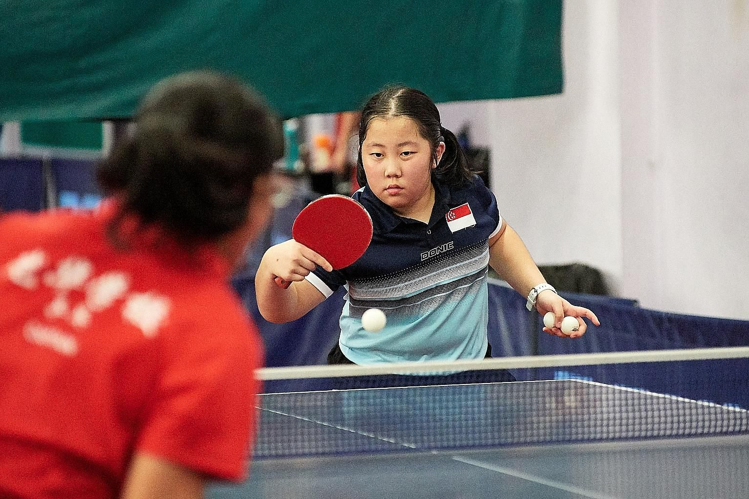 Lim Qi, who is ranked 11th in her age group, at a practice session at the Singapore Table Tennis Association. The 12-year-old excels not only in table tennis but also in her studies.