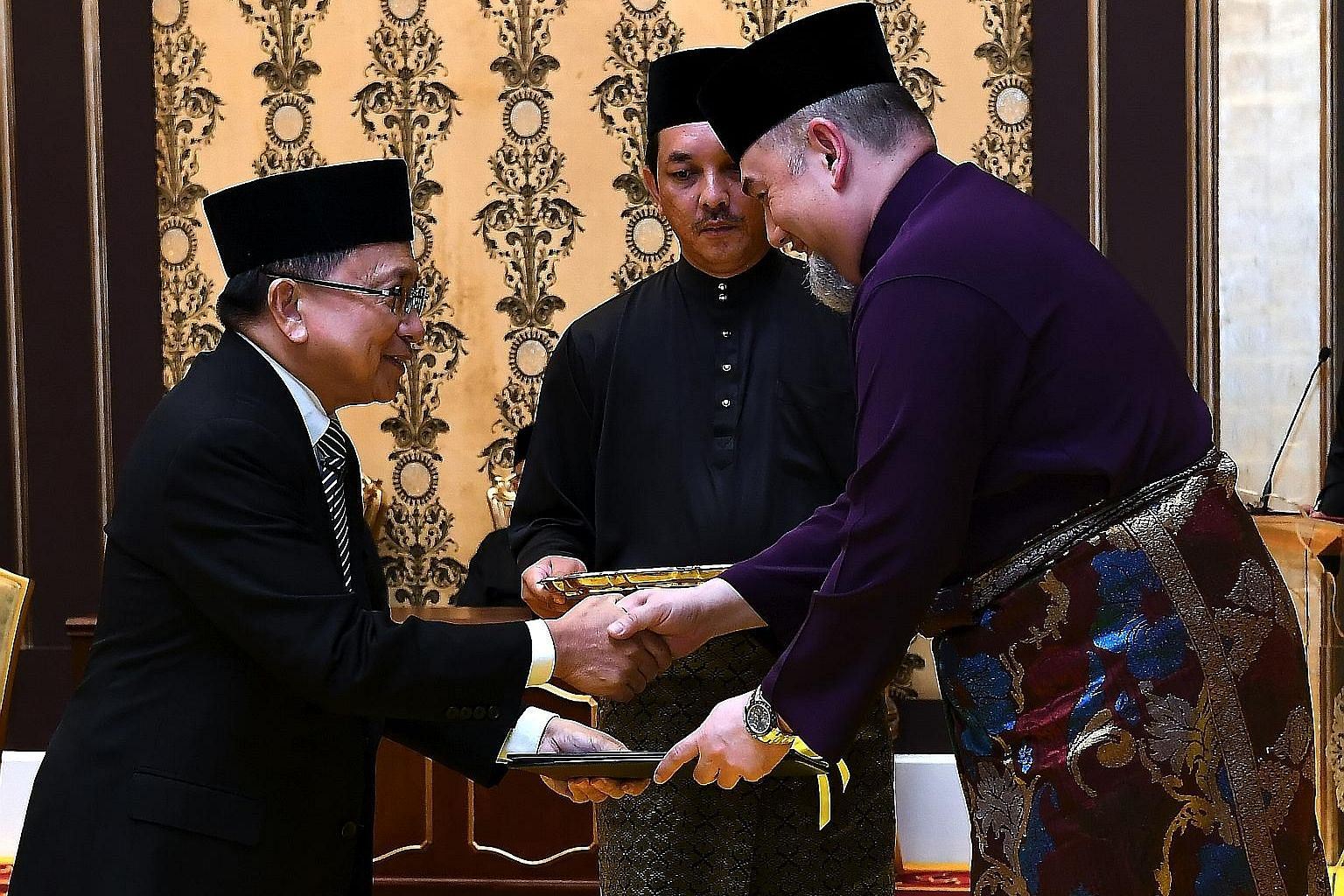 Malaysia's King, Sultan Muhammad V, handing the Chief Justice appointment letter to Tan Sri Richard Malanjum at Istana Negara last Wednesday.