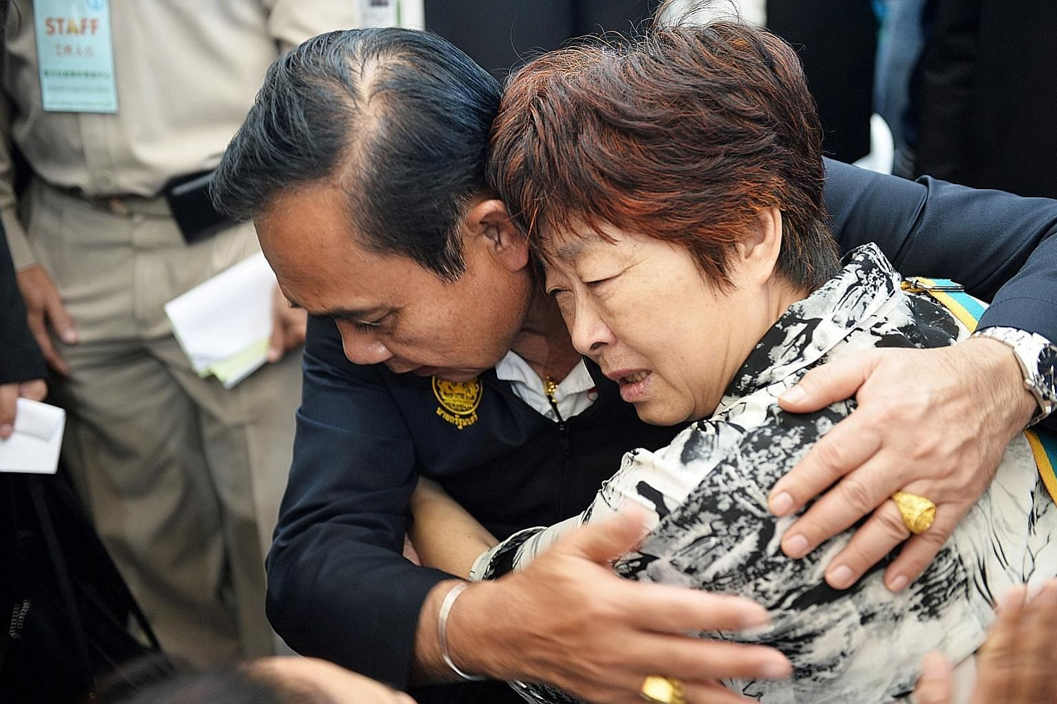 Thai Prime Minister Prayut Chan-o-cha comforting the relative of a victim of the Phuket boat accident.