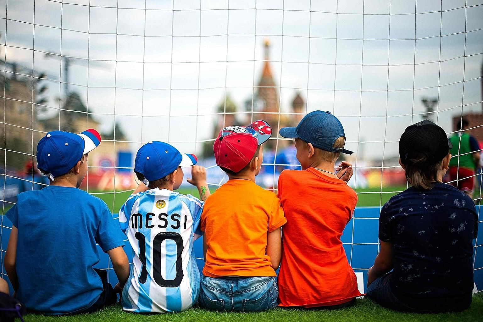 Left: Young fans watching a friendly amateur match between France and Croatia at the Red Square in Moscow as football fever swept across the nation during the World Cup. Below: The hosts defied expectations and knocked Spain out in a penalty shoot-ou