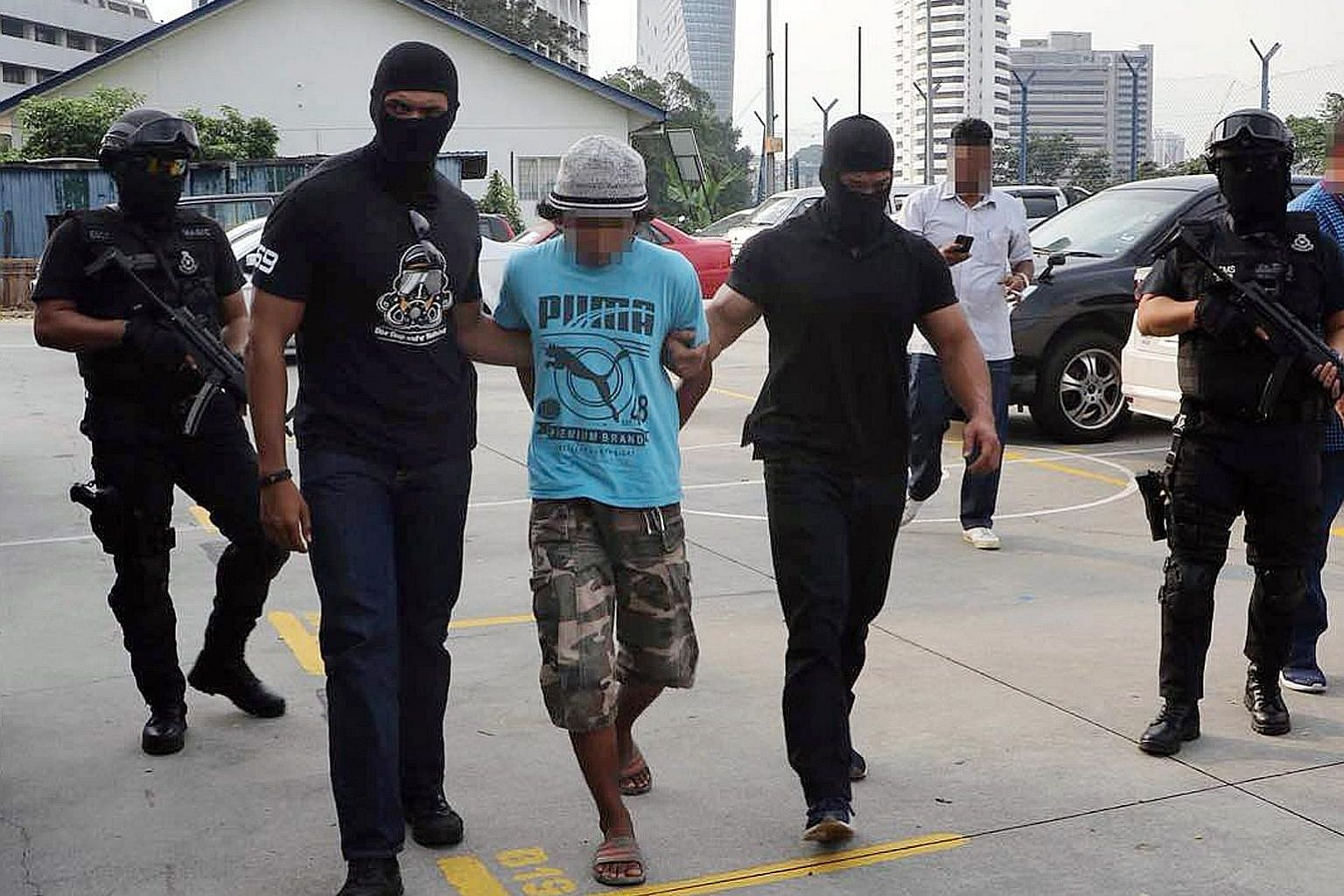 Malaysian police taking the suspected militants into custody. The arrests took place during a special operation in Johor, Terengganu, Selangor and Perak. One suspect had threatened online to kill Sultan Muhammad V, Malaysian Premier Mahathir Mohamad