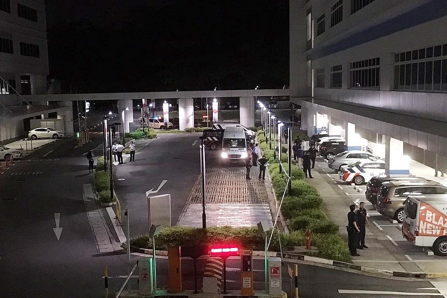 Police officers at the entrance to the sheltered carpark of ITE College Central in Ang Mo Kio, where a woman was believed to have been stabbed to death last night.