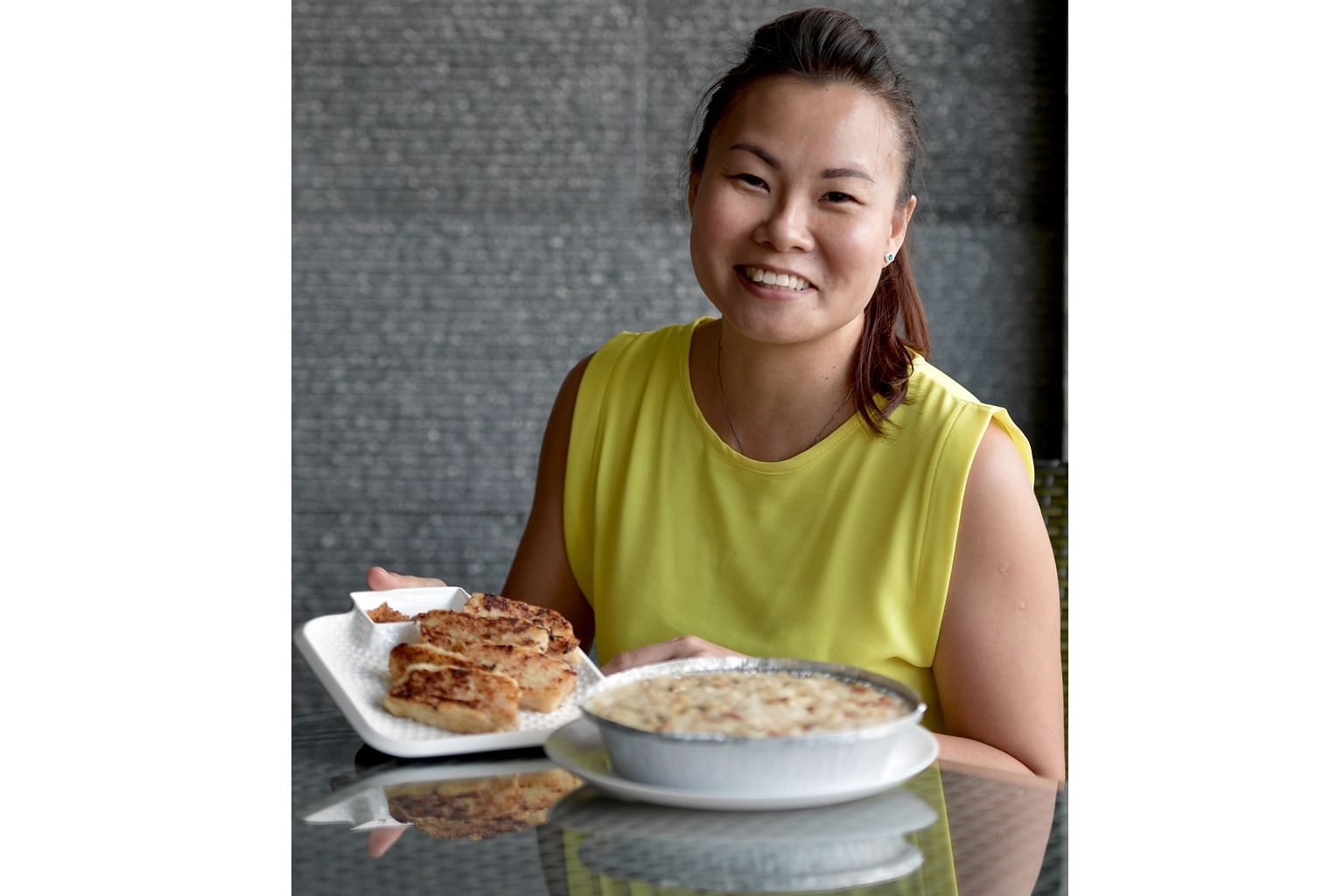 Ms Kelly Pang with the two versions of her radish cake - the steamed one (right) has a light and fluffy texture, while the fried one is soft inside with a crisp exterior.
