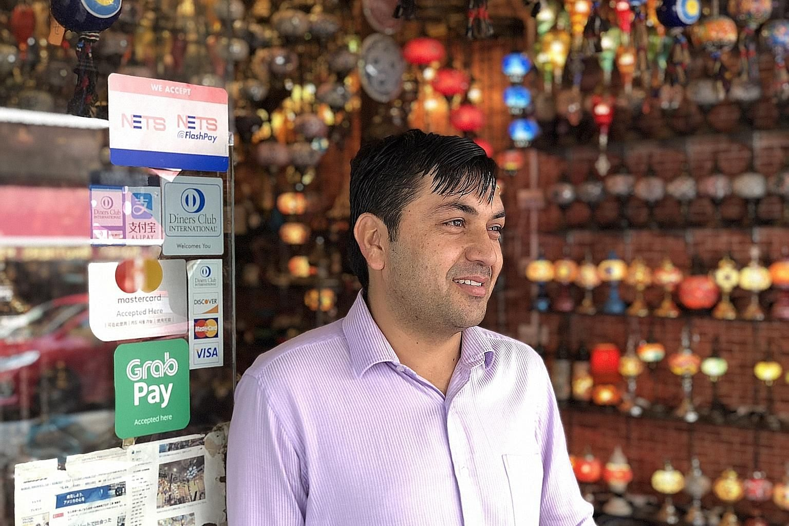 Mr Faizullah Saadullah operates family-owned retail shop Sufi Trading, which has used the GrabPay platform for three months and adopted Alipay recently. Mr Faizullah says the Alipay platform allows the Arab Street shop, which sells Turkish lamps, han
