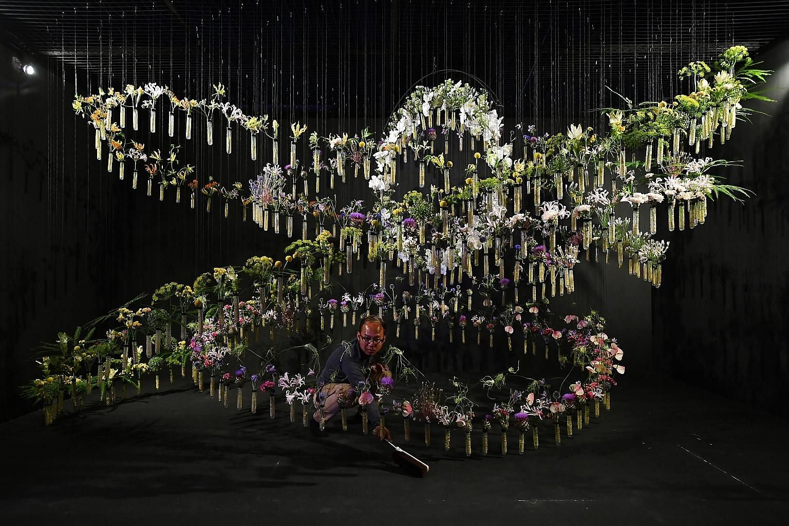 Left: Preparing cut flowers to be inserted into the test tubes. The suspended test tubes of the installation represent new life floating inside an amniotic sac. Above: Freelance florist Ivy Tay helping to prepare flowers for insertion into test tubes