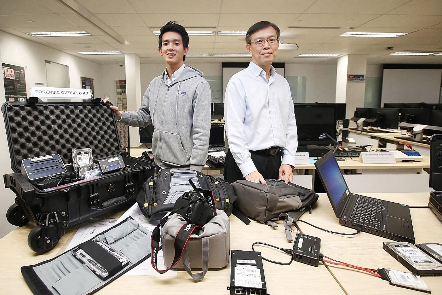 CSA National Cyber Incident Response Centre director Dan Yock Hau (right) and CSA senior consultant Lin Weiqiang with the forensic toolkits used to gather evidence at SingHealth's premises on the day of the attack. The equipment allows investigators
