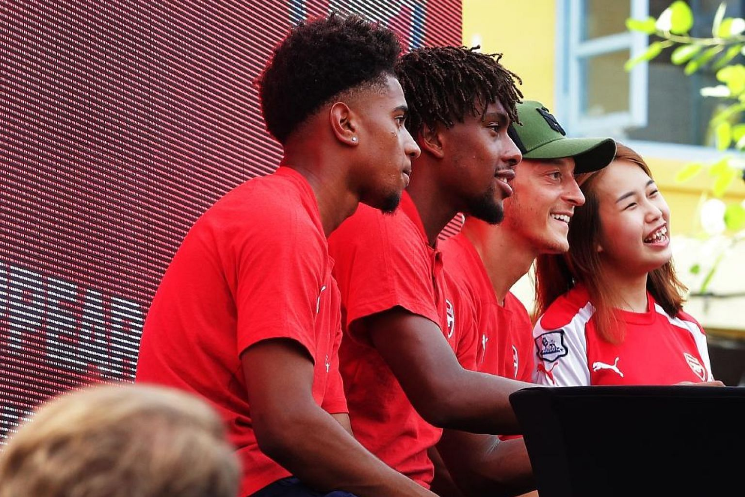 From left: Arsenal players Reiss Nelson, Alex Iwobi and Mesut Ozil with a fan at a meet-and-greet session at the House of Football in Clarke Quay yesterday.