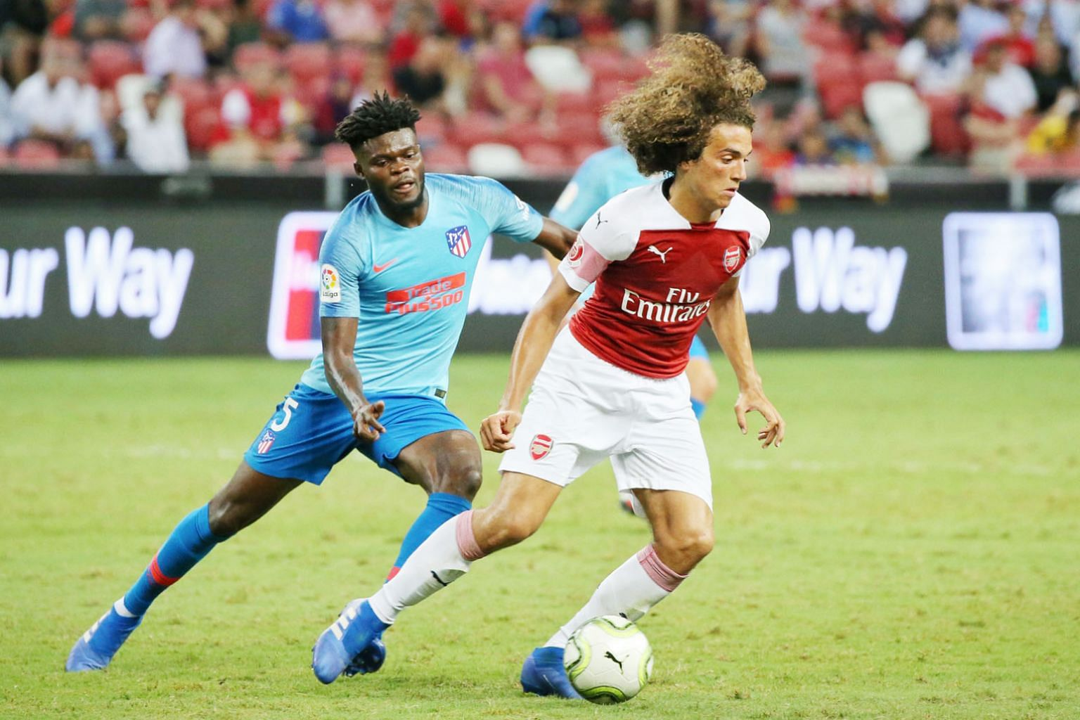 Arsenal's summer signing Matteo Guendouzi keeping the ball away from Atletico Madrid's Thomas Partey during their International Champions Cup match at the National Stadium. Left: Arsenal's Mesut Ozil walking out of the tunnel before the start of thei