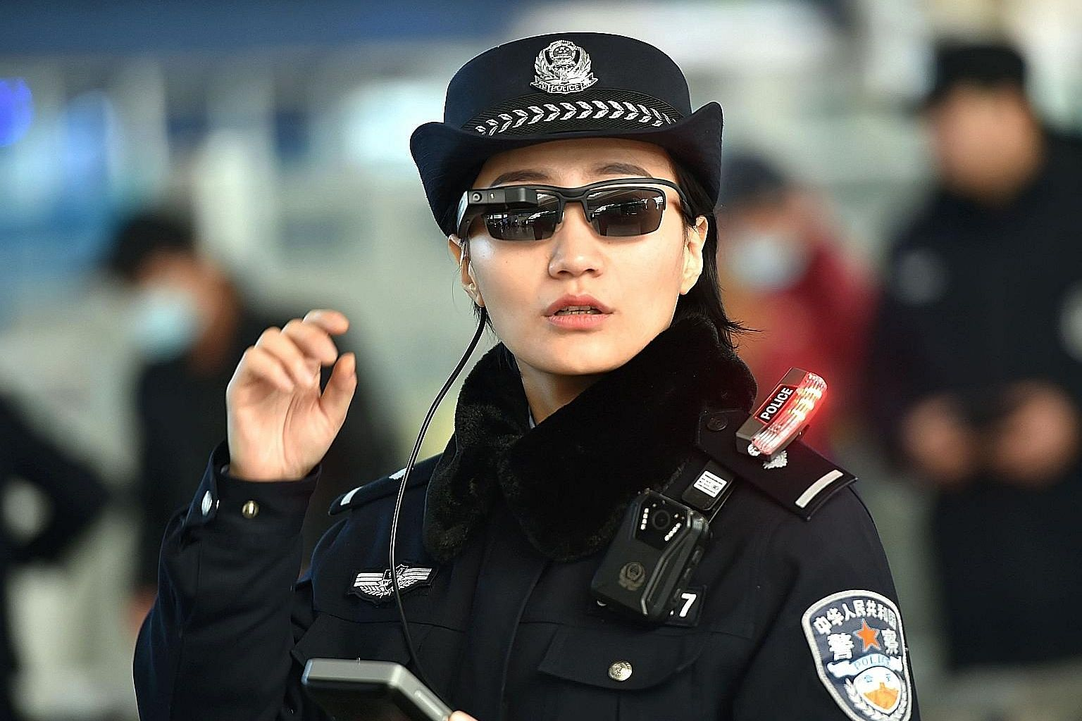 """A police officer wearing a pair of smartglasses with facial-recognition technology at Zhengzhou East Railway Station in Henan province. Beijing's stated aim is to have a national video surveillance network that is """"omnipresent, fully networked, alway"""