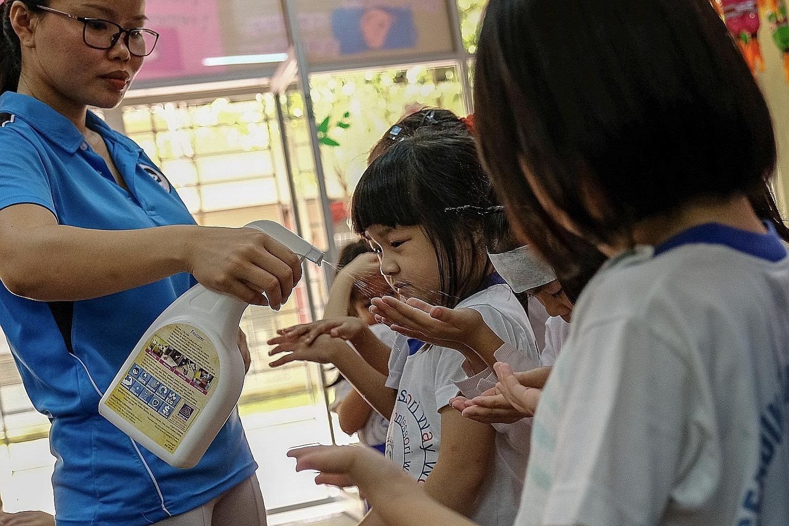 A teacher at a pre-school in Setapak, Kuala Lumpur, spraying sanitiser on children's hands (above) as a precaution against hand, foot and mouth disease, and checking a child's mouth (below) for symptoms of the disease last week. Most Malaysian states