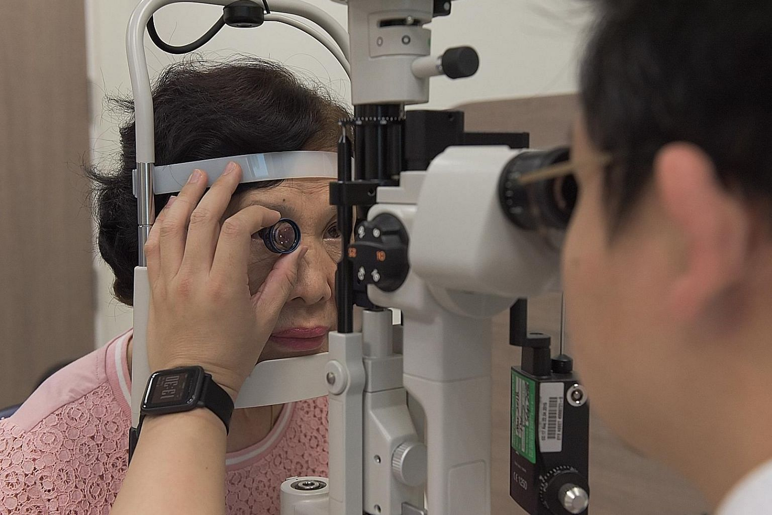 Singapore National Eye Centre consultant Gavin Tan doing a mock eye check (above) and eye injection with Madam Kueh Jee Kim. There has been a shift away from laser treatment to drugs injected into the eye to treat vision loss caused by diabetic retinopath