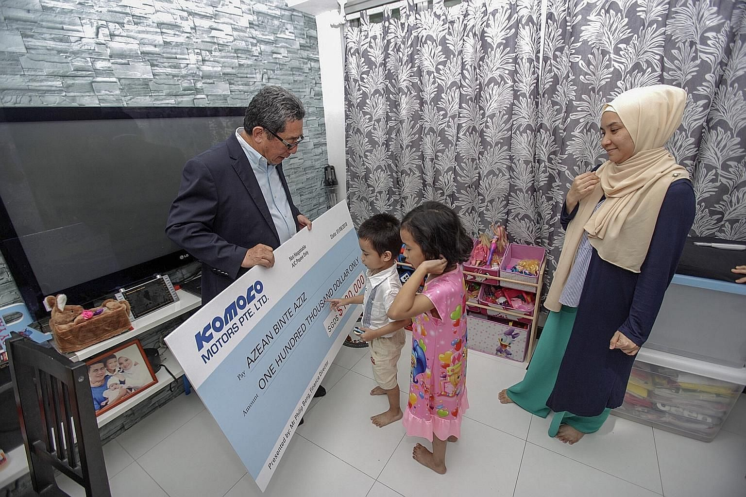 Komoco Motors finance director Philip Beng presenting a cheque of $100,000 to Azean Aziz - the widow of former Woodlands Wellington footballer Nur Alam Shah Yusoff, who died of a heart attack in May - and two of her three children, son Muhammad Royya