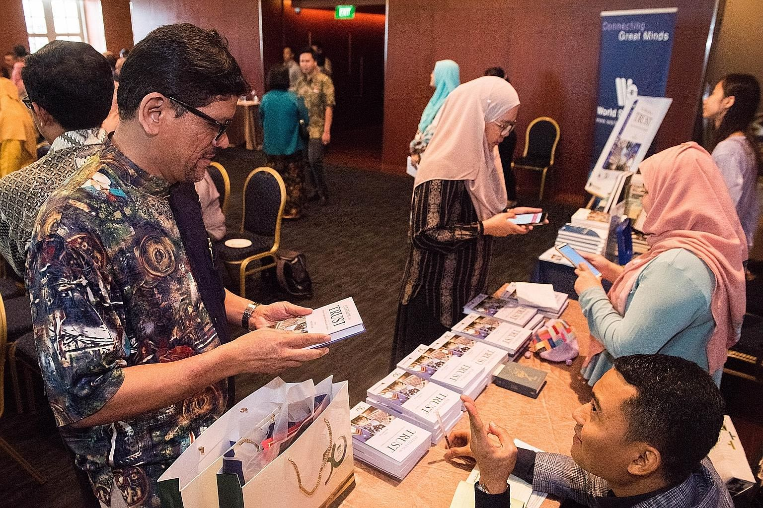 People visiting the selling booth to buy the Muis' 50th anniversary book, Fulfilling The Trust: 50 Years Of Shaping Muslim Religious Life In Singapore, during its launch at the Asian Civilisations Museum yesterday.
