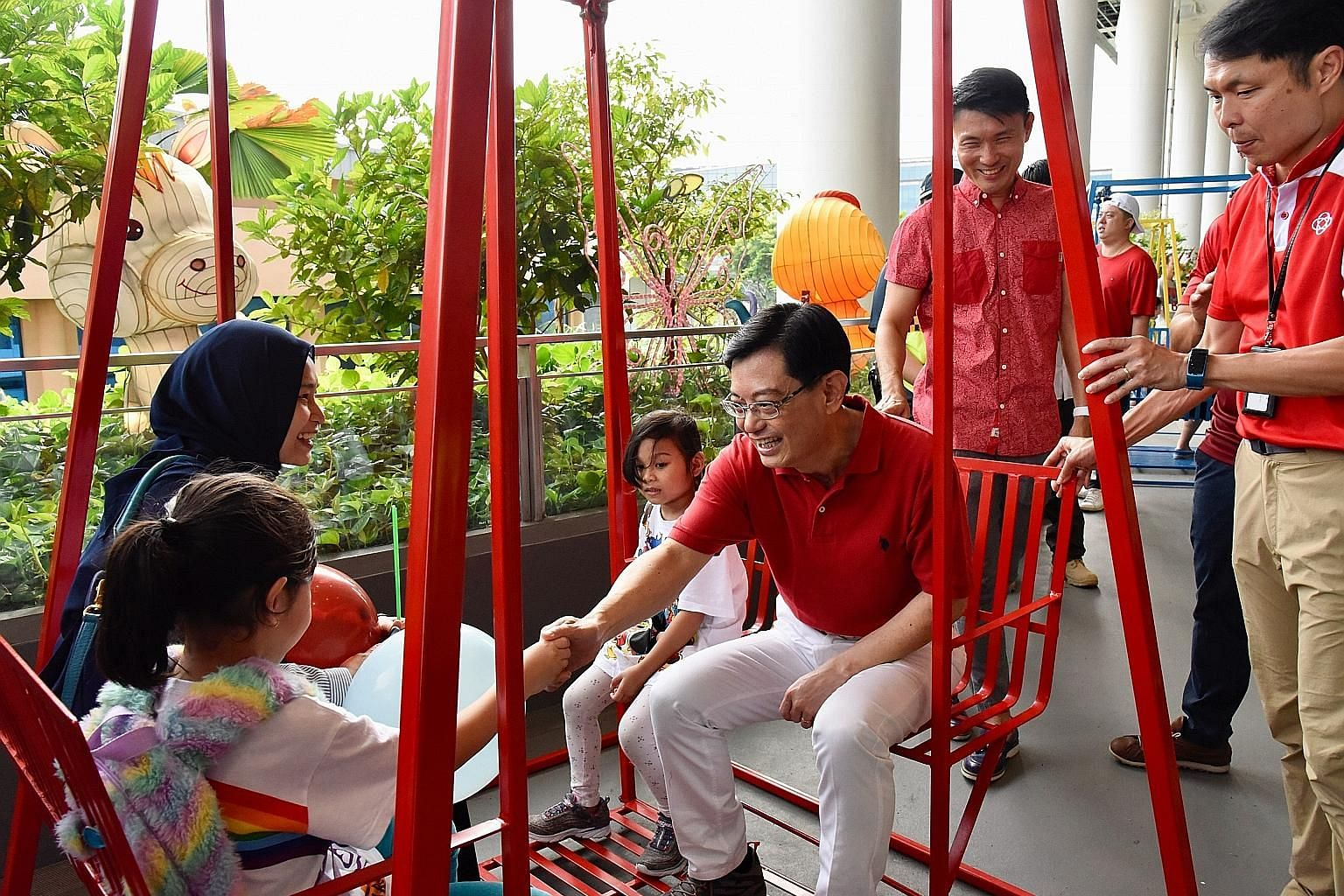 Finance Minister and Tampines GRC MP Heng Swee Keat greeting a family on a swing at the All-Inclusive Playground in Our Tampines Hub yesterday. Rock climbers attempting to complete a 53km rock wall climb yesterday at the Rock School in Our Tampines H