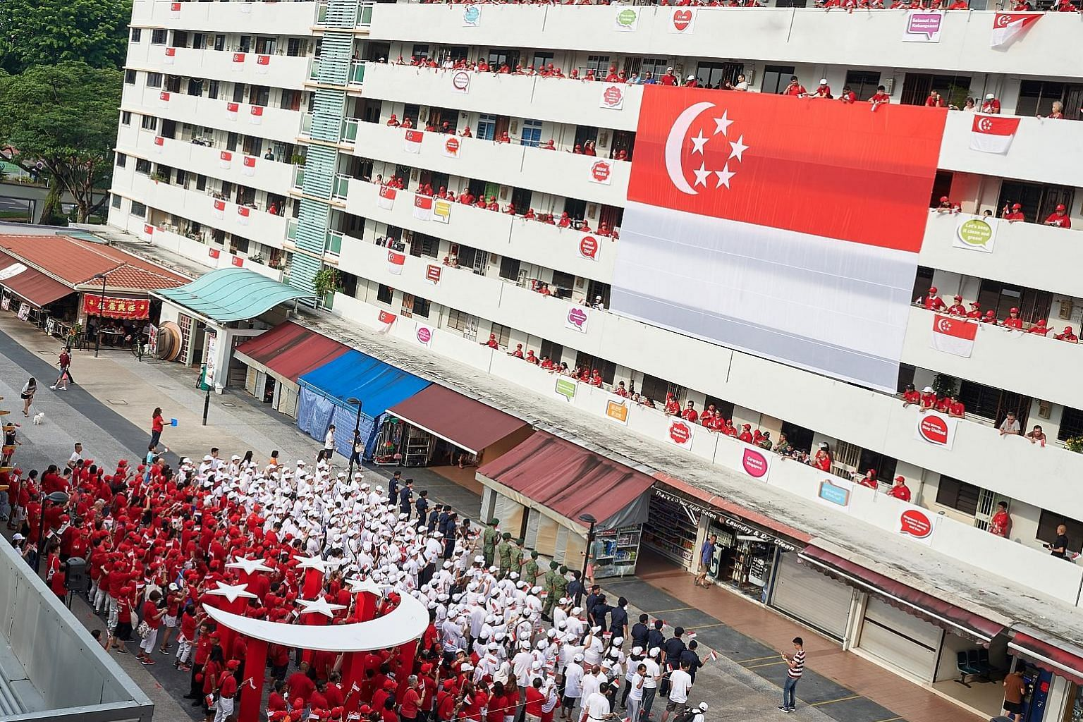 Bedok residents dressed in red and white form a human flag between Blocks 16 and 18 on Bedok South Road, mirroring a giant 12m-by-8m Singapore flag hung on the facade of Block 18. The block was also decorated with slogans such as Majulah Singapura as