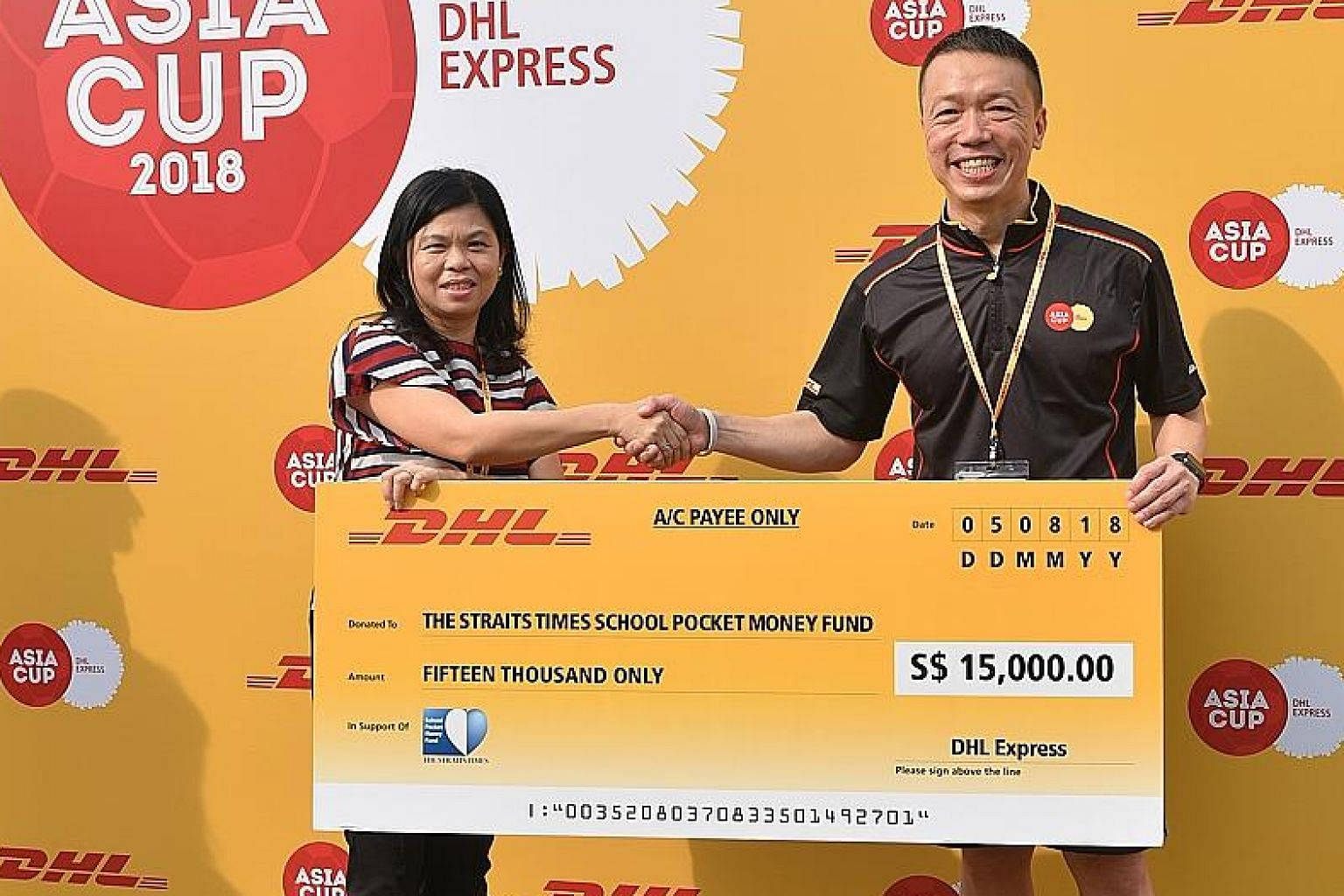 Ms Tan Bee Heong, General Manager, STSPMF, receiving the cheque from Ken Lee, CEO DHL Express Asia Pacific. DHL organised a football clinic for 20 ST School Pocket Money Fund beneficiaries.