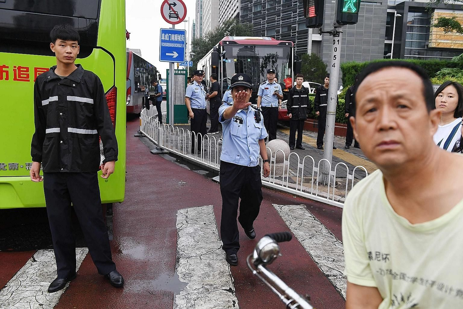 Police officers in front of the China Banking Regulatory Commission yesterday, as petitioners from all over China planning to protest against losses sustained on peer-to-peer lending platforms were loaded into buses and driven away under police escor