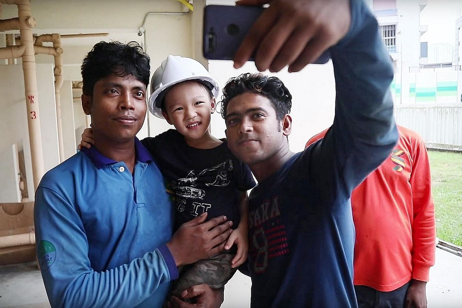 """Jake in the arms of """"Red Helmet Uncle"""", one of the foreign workers he befriended after he saw them carrying out upgrading works near his home."""