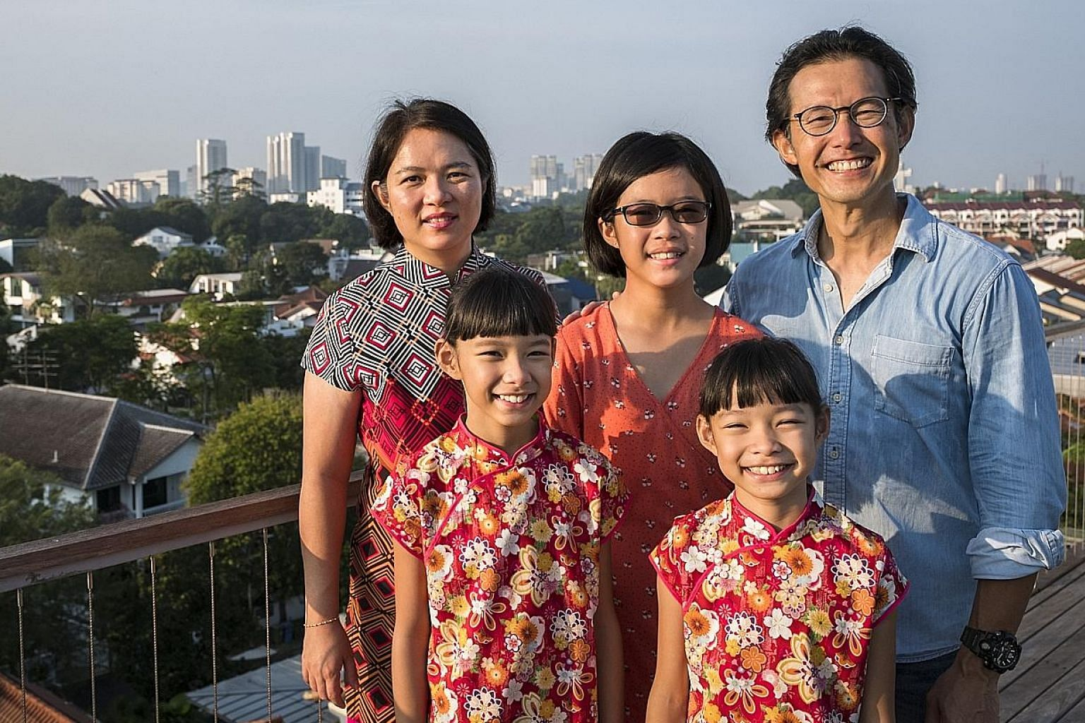Mr Andrew Chew and his wife Jennifer Kiing (left) with their children - eldest daughter Elizabeth (centre) and twins Esther (foreground left) and Emma.