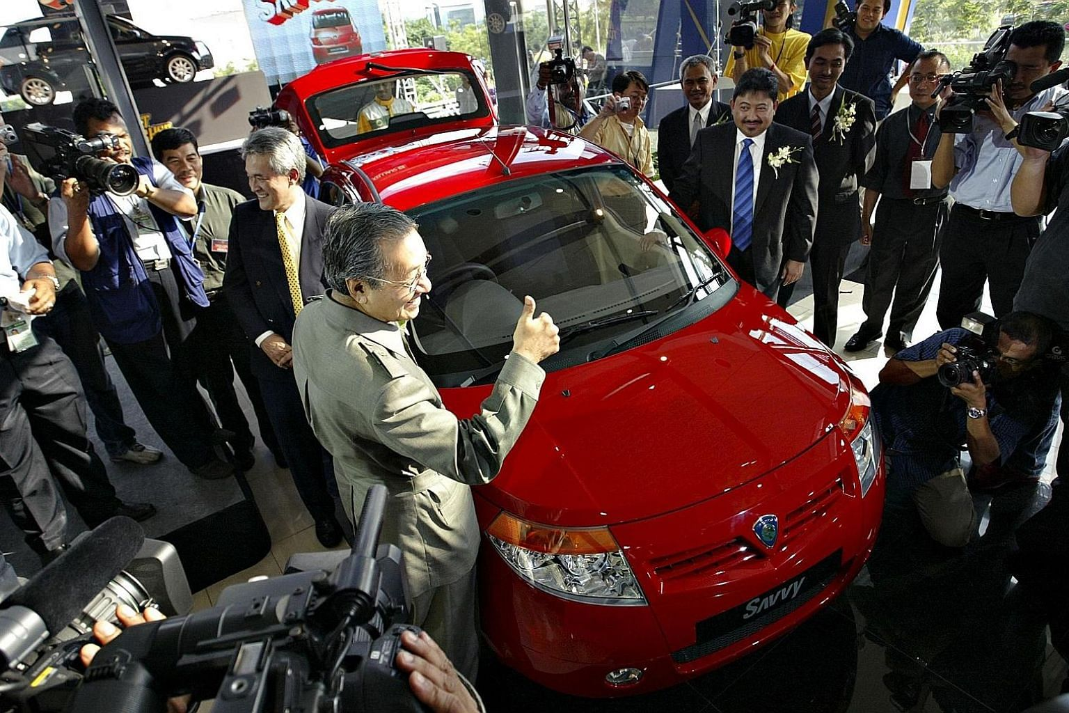 Tun Dr Mahathir Mohamad giving a thumbs up at the launch of the then new model Proton Savvy on June 8, 2005. The Proton national car project, Malaysia's first, was launched by Dr Mahathir in 1983. Perodua, the second national car project, was establi
