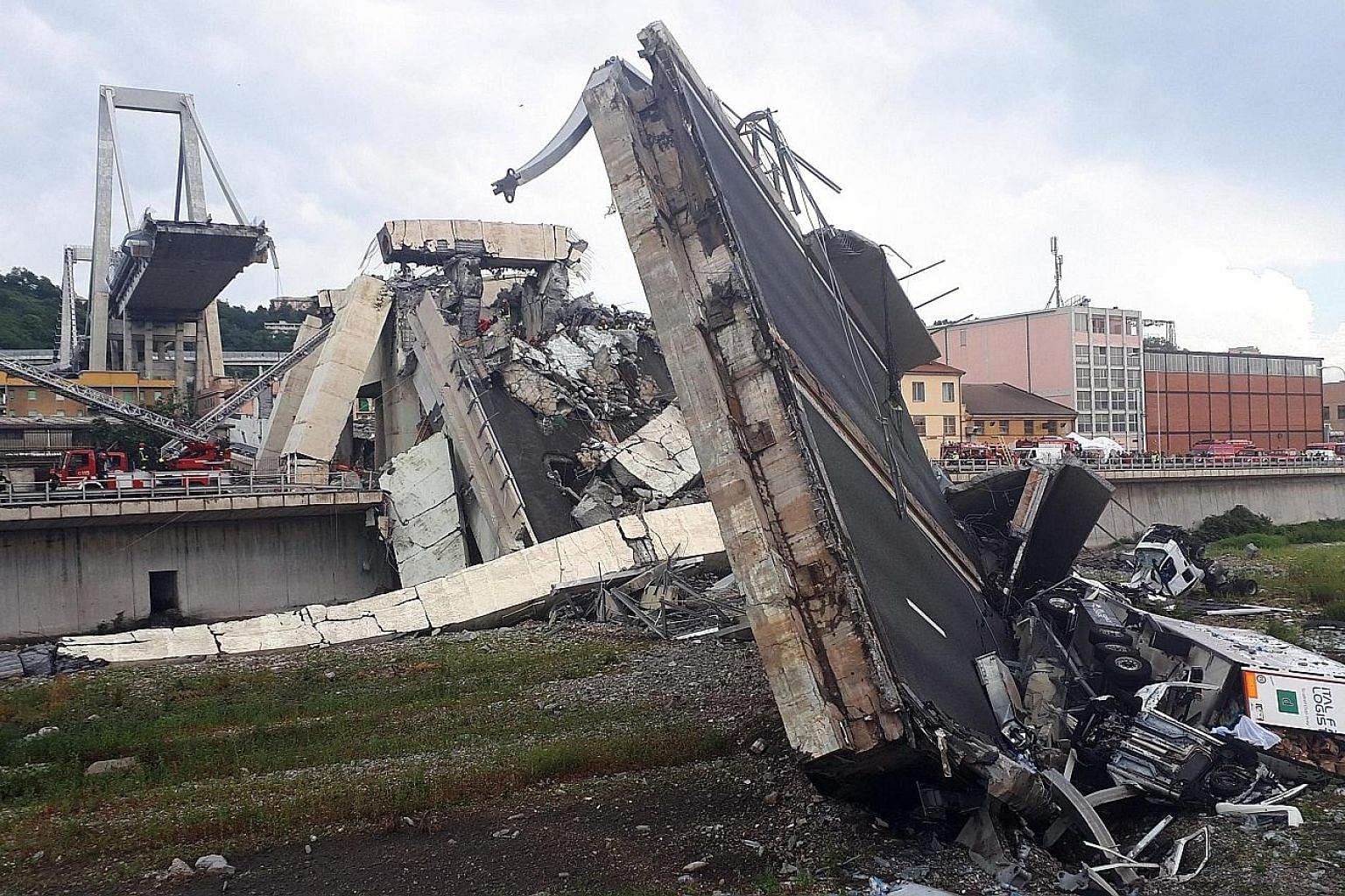 Rescuers at work amid the rubble after a large section of a motorway bridge collapsed during a rainstorm yesterday in the northern Italian city of Genoa. Sky Italia television said four people had been pulled from the rubble.