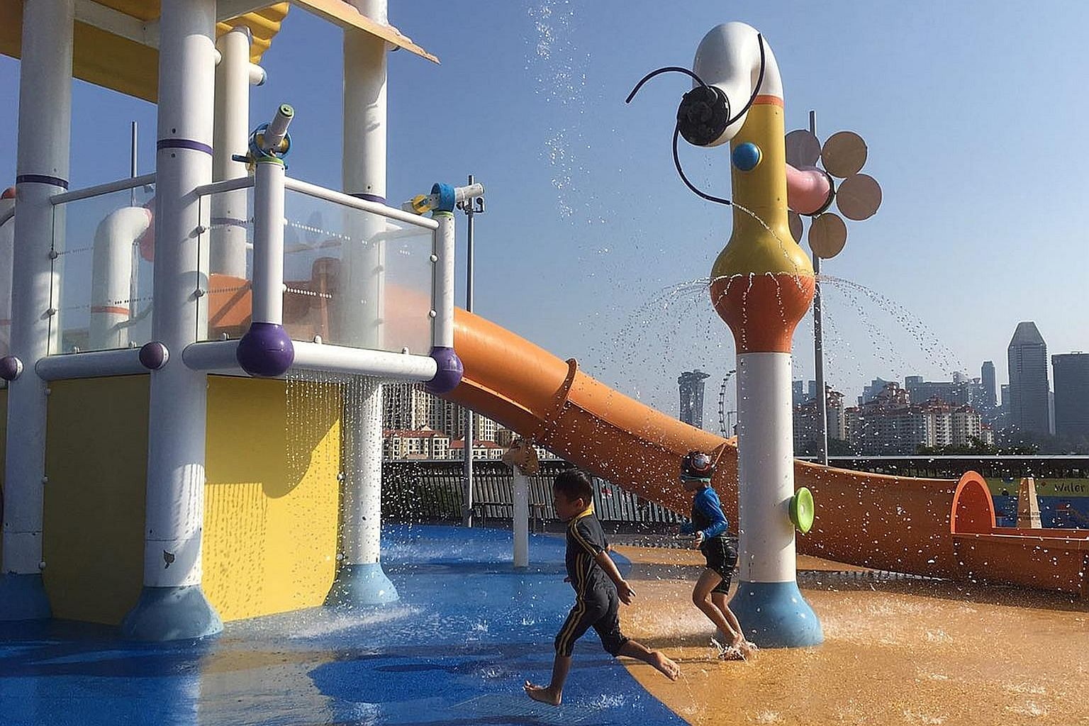 Above: Children cooling off at the water play area of the Singapore Sports Hub yesterday. Left: A tourist trying to keep cool in the searing heat in Chinatown yesterday.