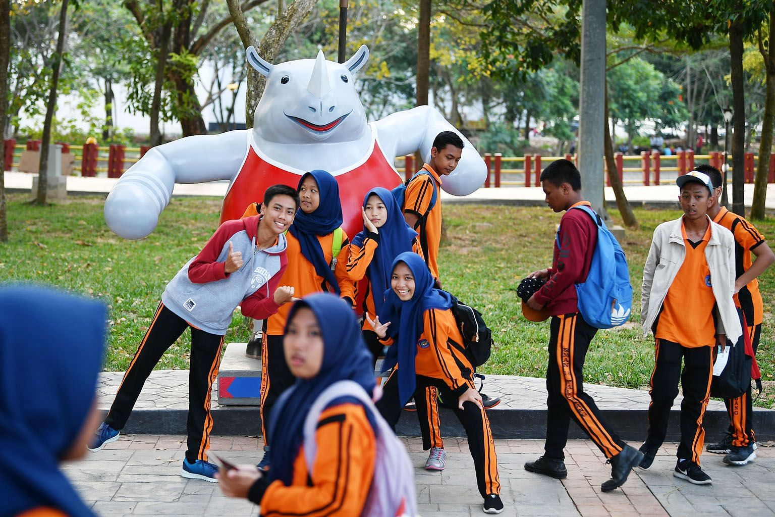 Above: Students posing with one-horned rhino Kaka, one of the mascots, outside Gelora Sriwijaya Stadium, the main venue in the Asian Games co-hosting city Palembang. Left: Scoot cabin crew holding the Singapore flag before departing for Palembang wit