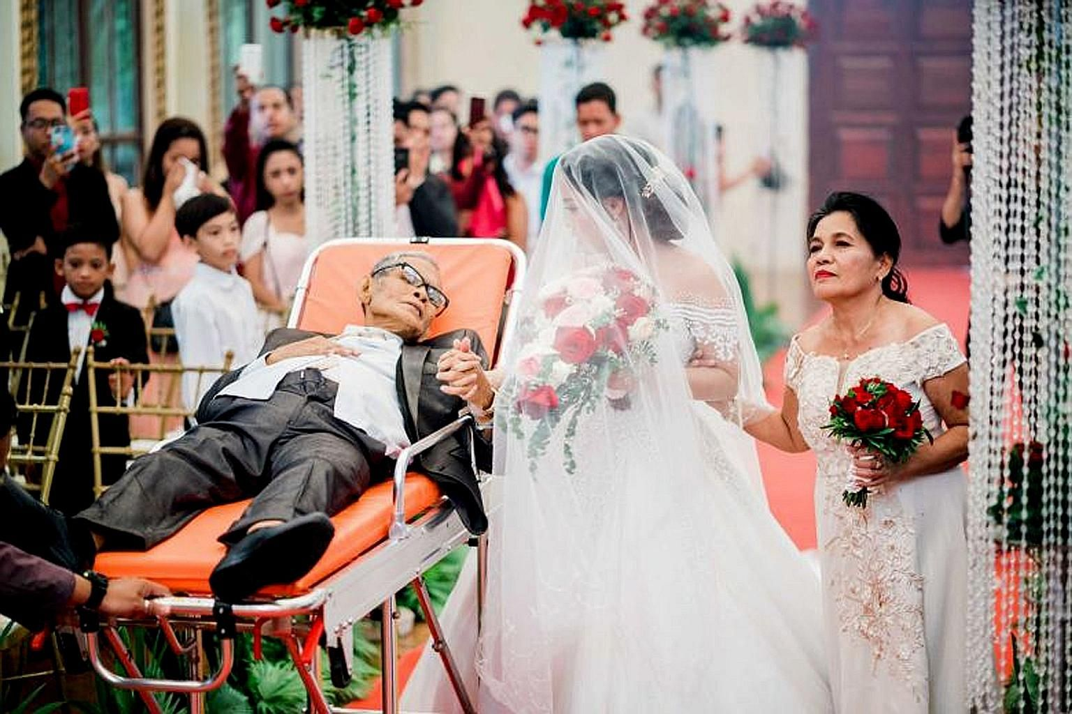 Ms Charlotte Gay Villarin has her fingers laced around those of her father - Mr Pedro Villarin - who, despite being weak, looks lovingly at his daughter from a stretcher, which is being pulled down the aisle. On the right is the bride's mother.