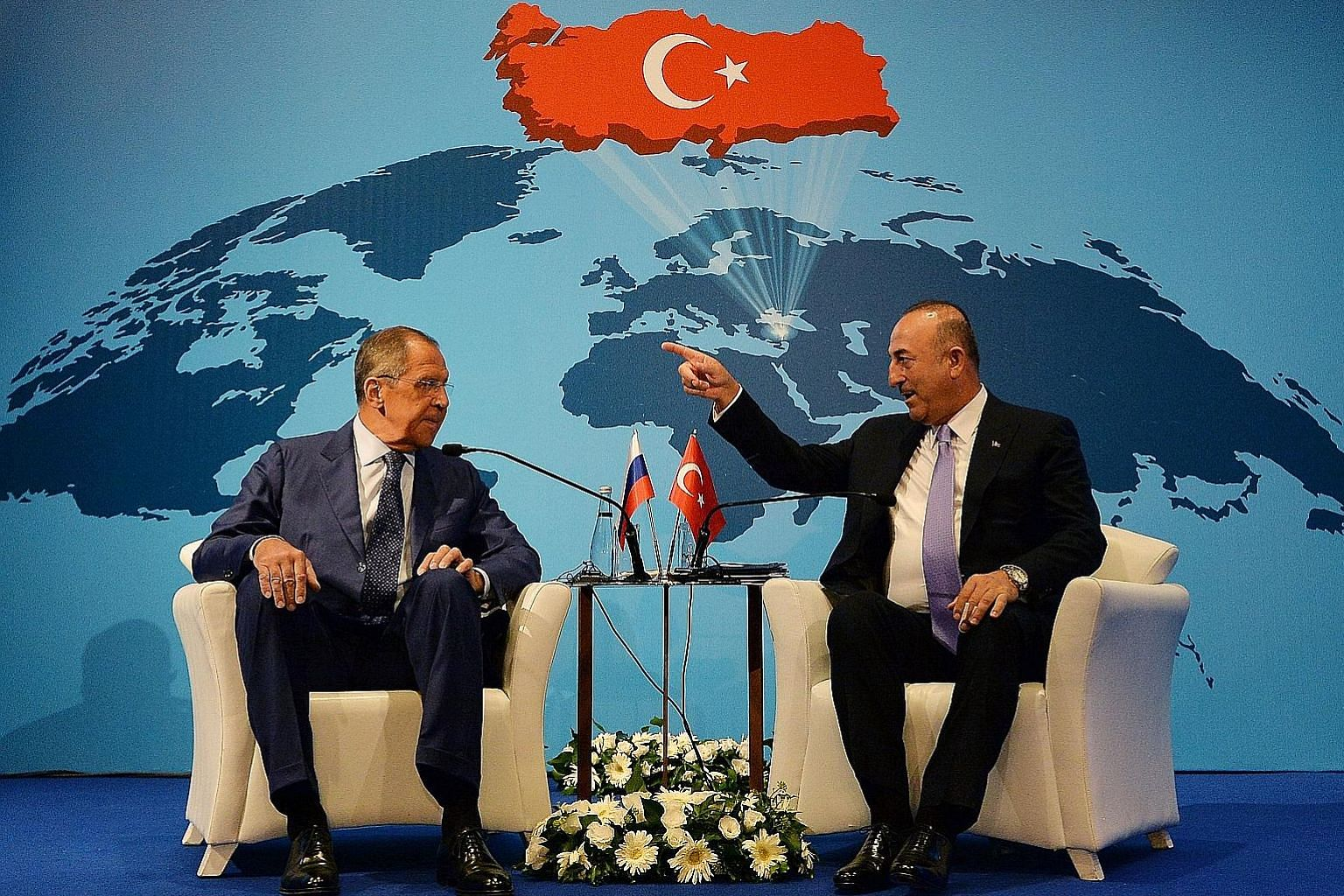 Russian Foreign Minister Sergey Lavrov (far left) meeting his Turkish counterpart Mevlut Cavusoglu in Ankara on Tuesday. Both countries are drawing closer to each other largely because of the US imposing sanctions on them, says the writer.