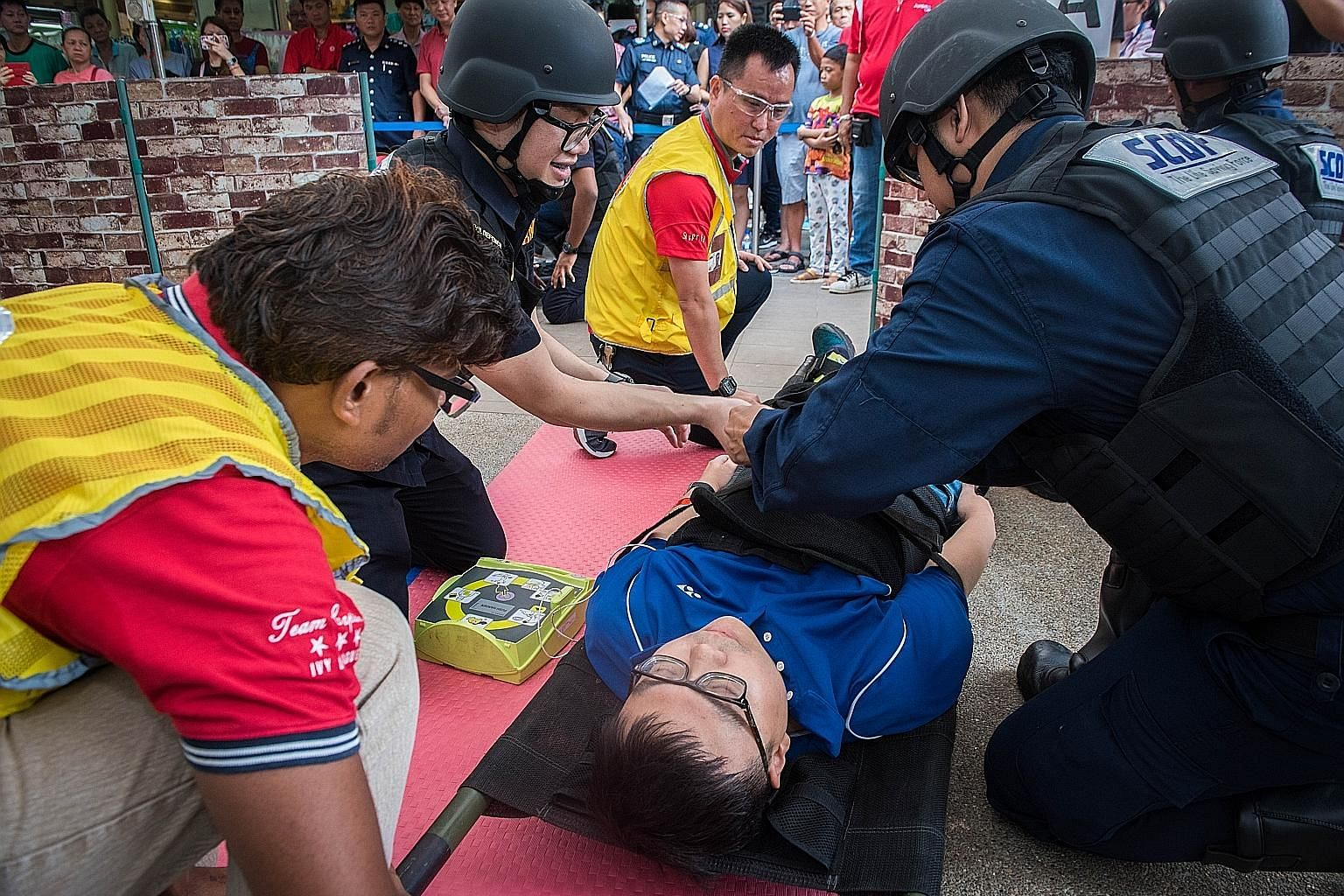 "Singapore Civil Defence Force (SCDF) officers attending to a ""victim"", following a drill simulating an attack by gunmen yesterday. Shots had rung out earlier in Jurong West, as gunmen attacked the Sunday morning crowd at a market. Fortunately, it was"