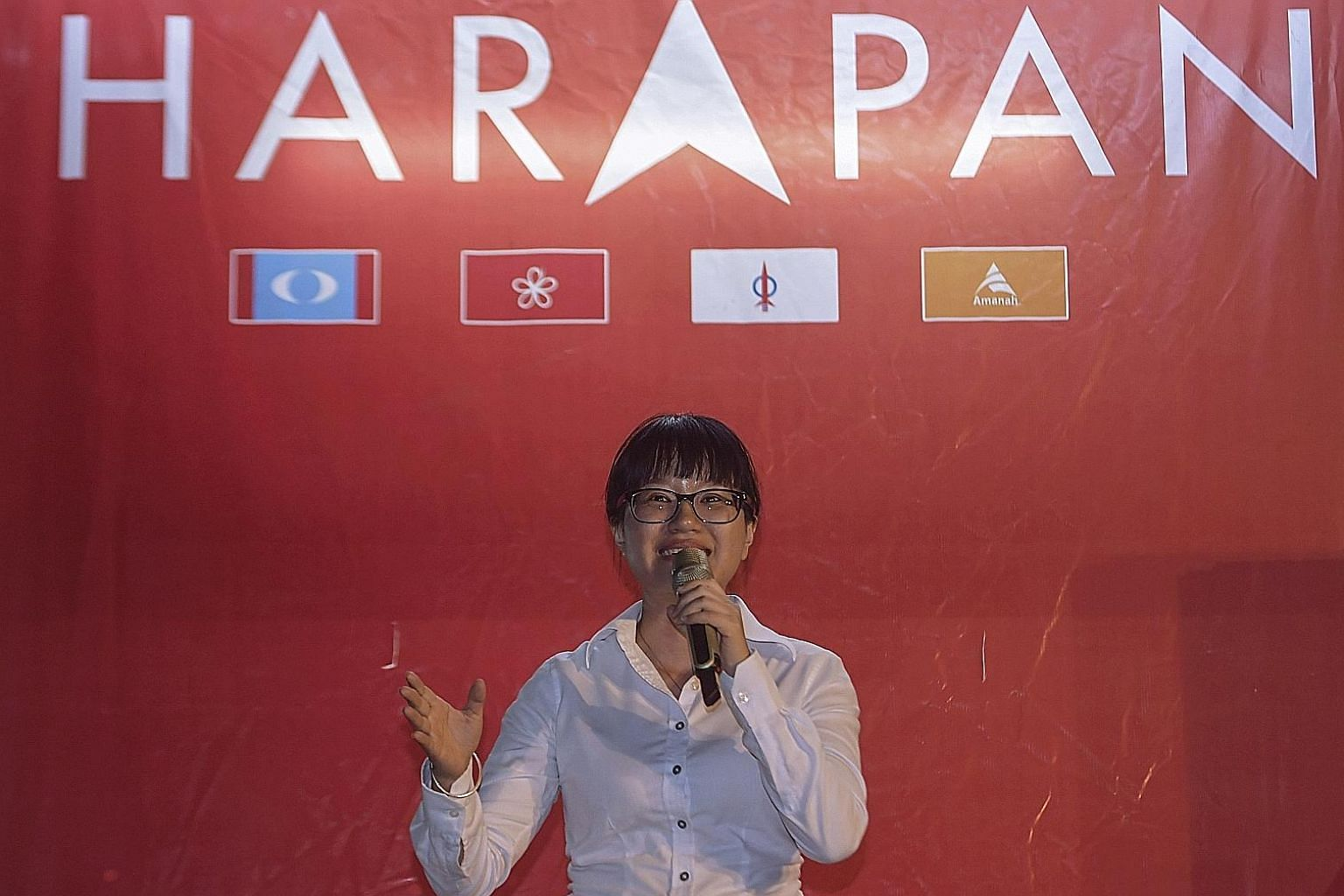 """Pakatan Harapan candidate Wong Siew Ki in front of a version of the PH logo, which has an arrowhead replacing the letter """"A"""" in the middle of the word """"Harapan"""". Malaysian Chinese Association candidate Tan Chee Teong (third from left) and other party"""
