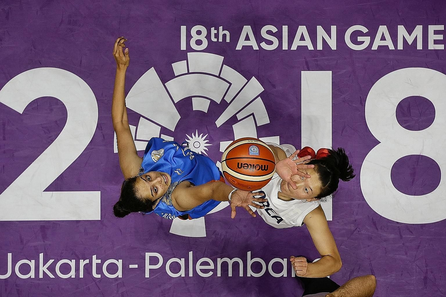 India's Rajapriyadharshini Rajaganapathi and Unified Korea's Ro Suk Yong vying for the ball in a women's basketball match at the Asian Games.