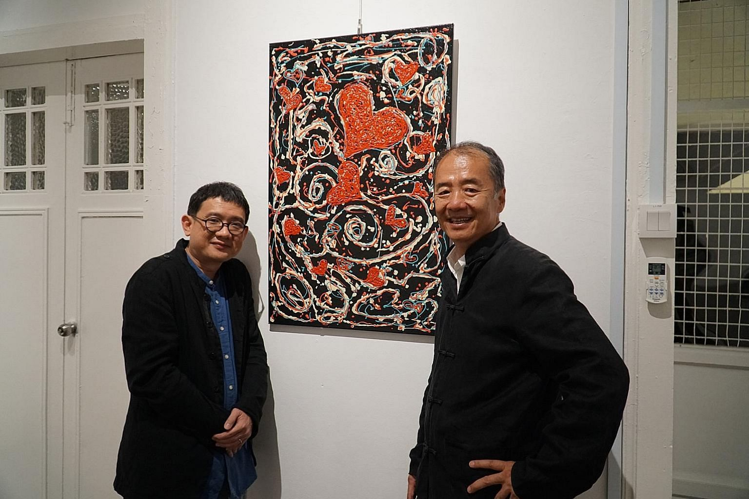 Mr Phan Ming Yen (left), director of non-profit organisation Global Cultural Alliance, and artist Sun Yu Li, with one of the inmates' art works on display at arts centre Temenggong House 18/20.