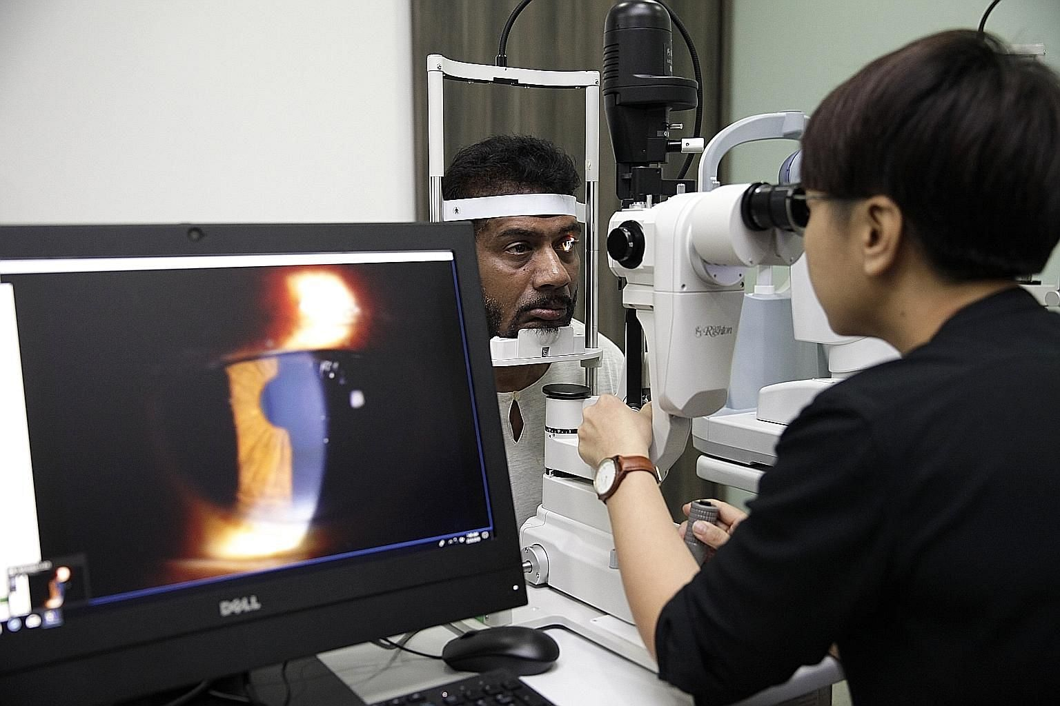 Optometrist Quek Zuoling giving Mr Chinnayah Ponnusamy a check-up at the eye clinic at Hougang Polyclinic, one of six primary-care facilities chosen for an initiative to step up eye care in the community.