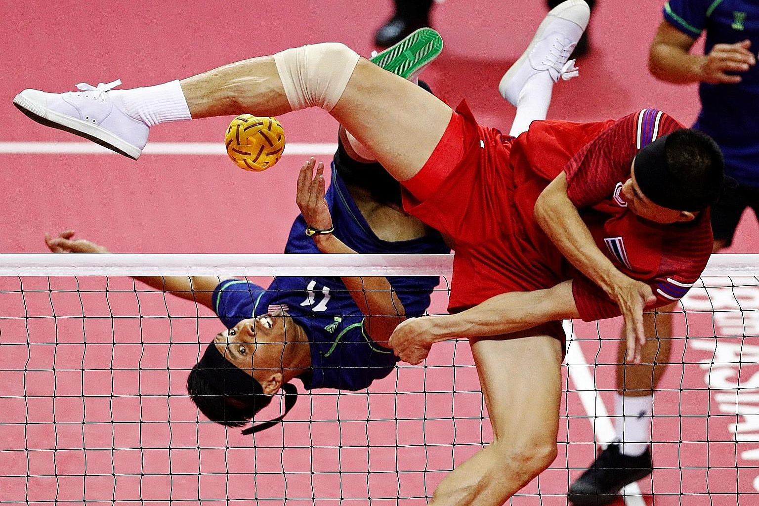 Muhamad Norhaffizi Abdul Razak of Malaysia and Anuwat Chaichana of Thailand (in red) battling it out in the men's regu gold-medal match yesterday. The Thais, the undisputed sepak takraw kingpins, added two more golds to their 22 from previous Asian G