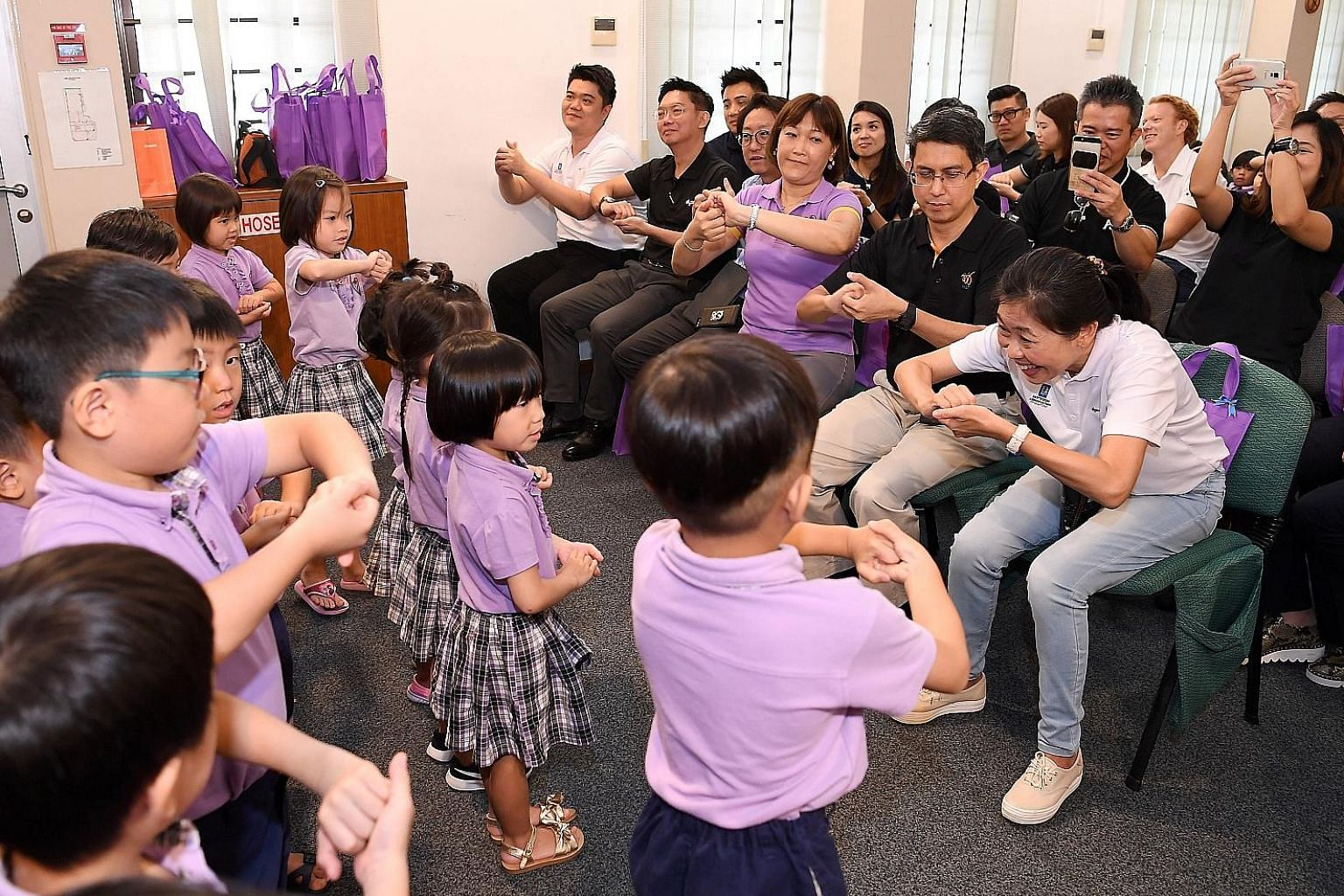 From right: RAS president Tan Puay Hoon, Associate Professor Muhammad Faishal Ibrahim and Ms Brands Ng, director of Cherie Hearts @ Charlton, joining in as the pre-schoolers put on a performance, showing how to wash their hands properly.