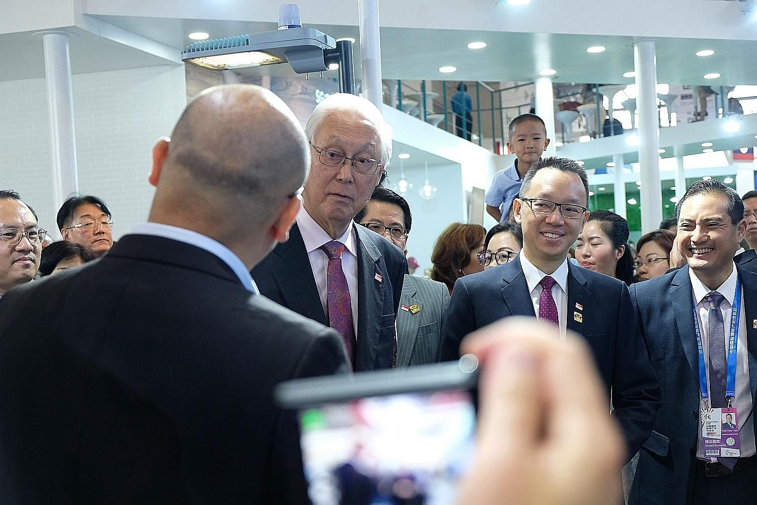 Emeritus Senior Minister Goh Chok Tong and Senior Parliamentary Secretary for Trade and Industry and Foreign Affairs Tan Wu Meng (second from right) on a tour of the Singapore pavilion at the Smart China Expo in Chongqing yesterday.