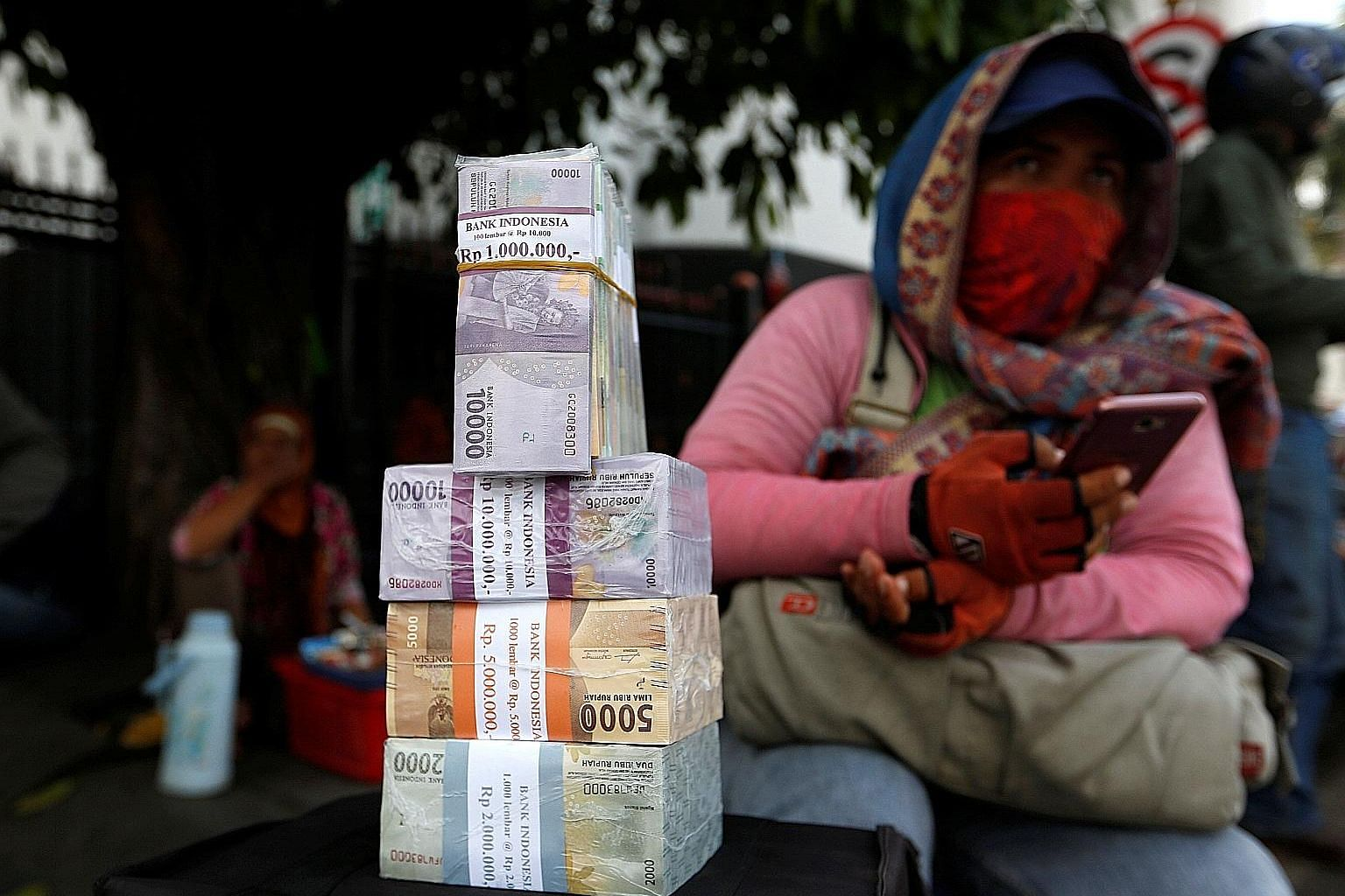 A woman who provides change for large banknotes with stacks of Indonesian rupiah on a street in Jakarta. The currency has lost nearly 8 per cent of its value against the US dollar since the beginning of the year. And this month, the Bank of Indonesia