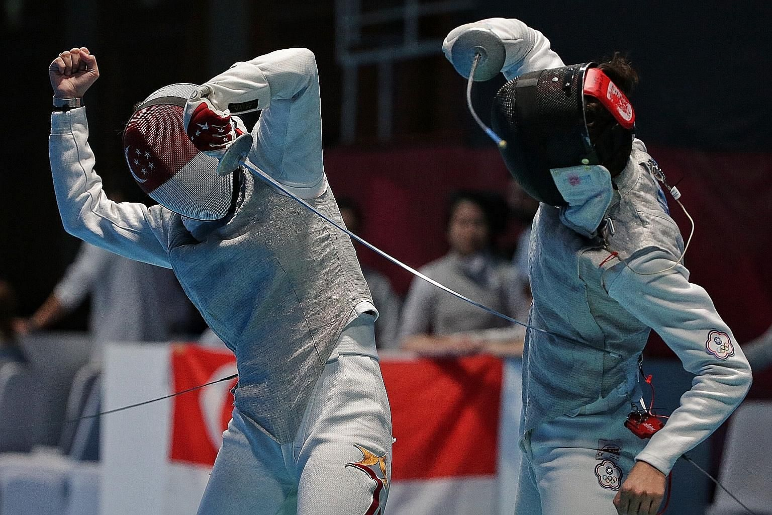 Singapore's Amita Berthier goes on the offensive against Chinese Taipei's Yang Chin-man during their bout in their women's foil team quarter-final at the Jakarta Convention Centre yesterday.