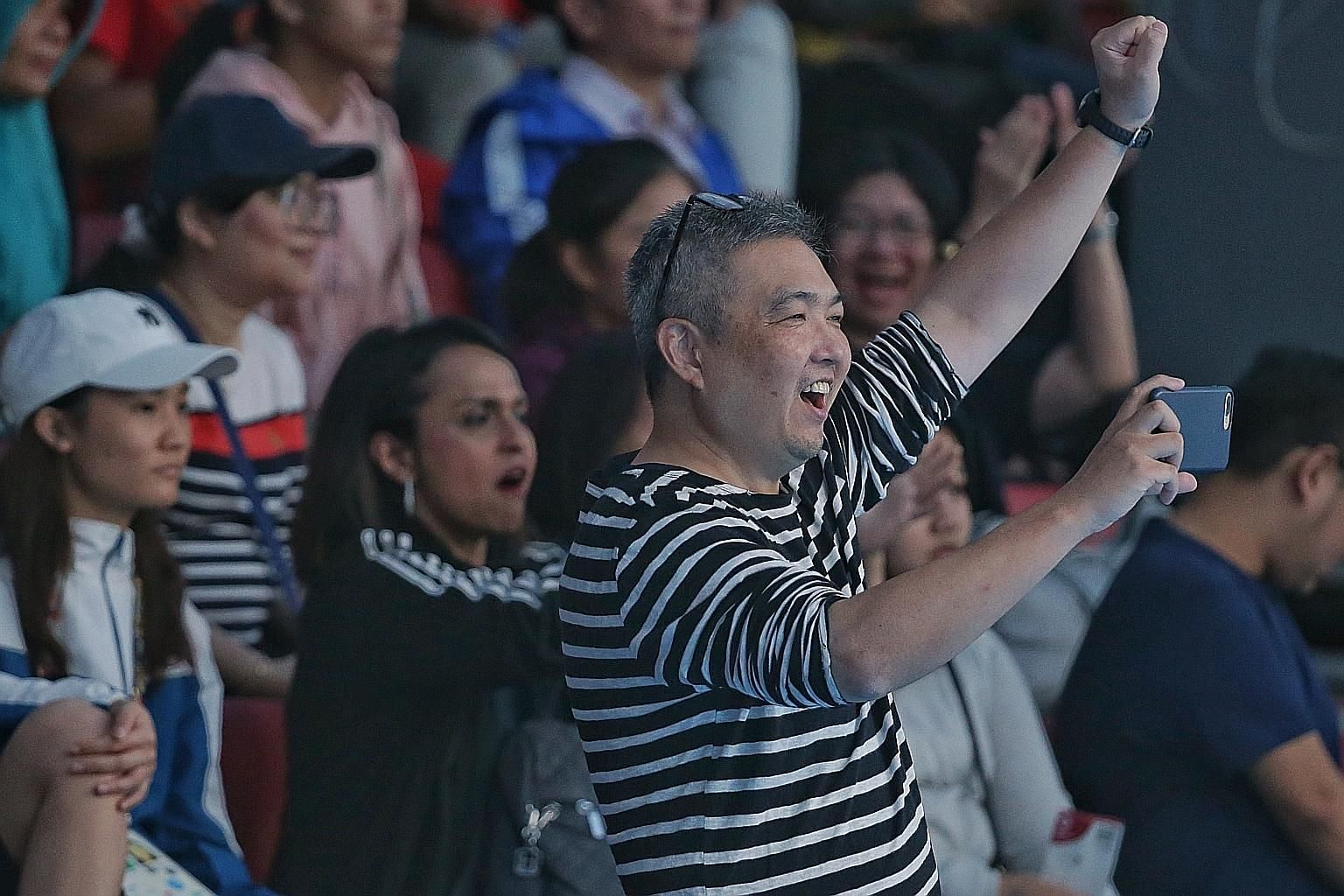 Fencer Maxine Wong's father, Philip (front) and mother Chan Bee Bee (rear, with glasses and clapping), and fencer Amita Berthier's mother Uma (behind Philip) watching them during the Singapore women's foil team's 45-14 semi-final loss to China in Jak