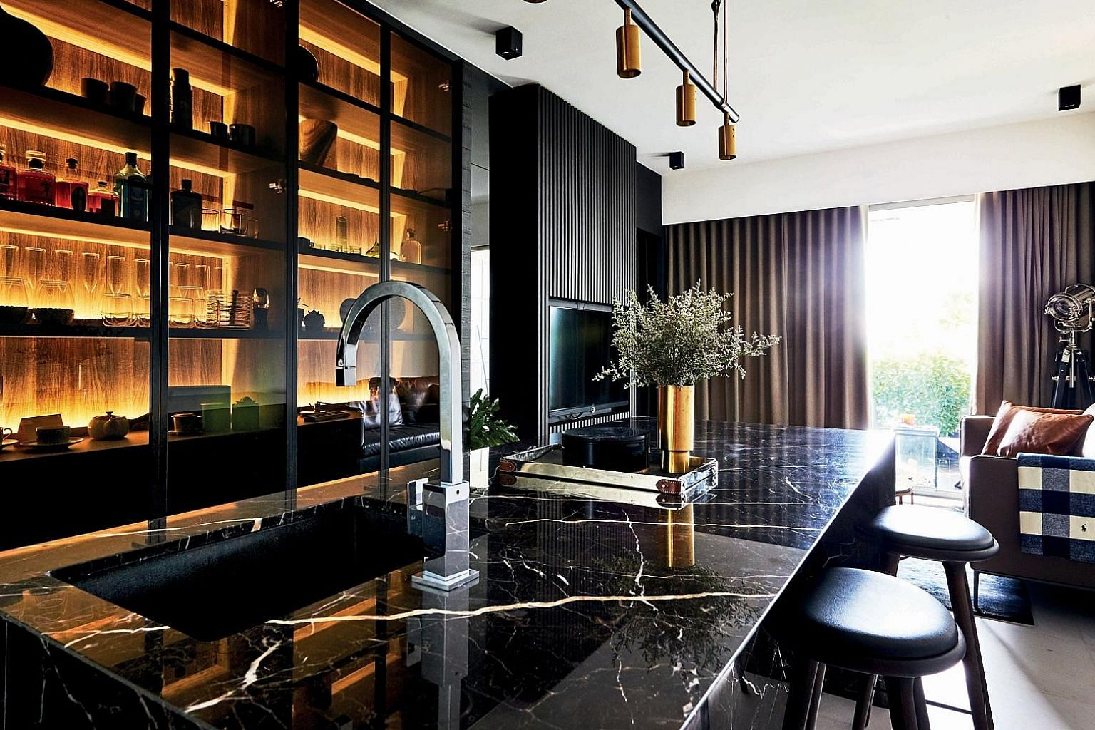 The sink, using Nero Marquina marble, was moved outside of the bathroom to create a bigger vanity area. The large island kitchen, holding the sink, dishwasher and wine fridge, occupies a central part of the apartment as the home owners entertain ofte