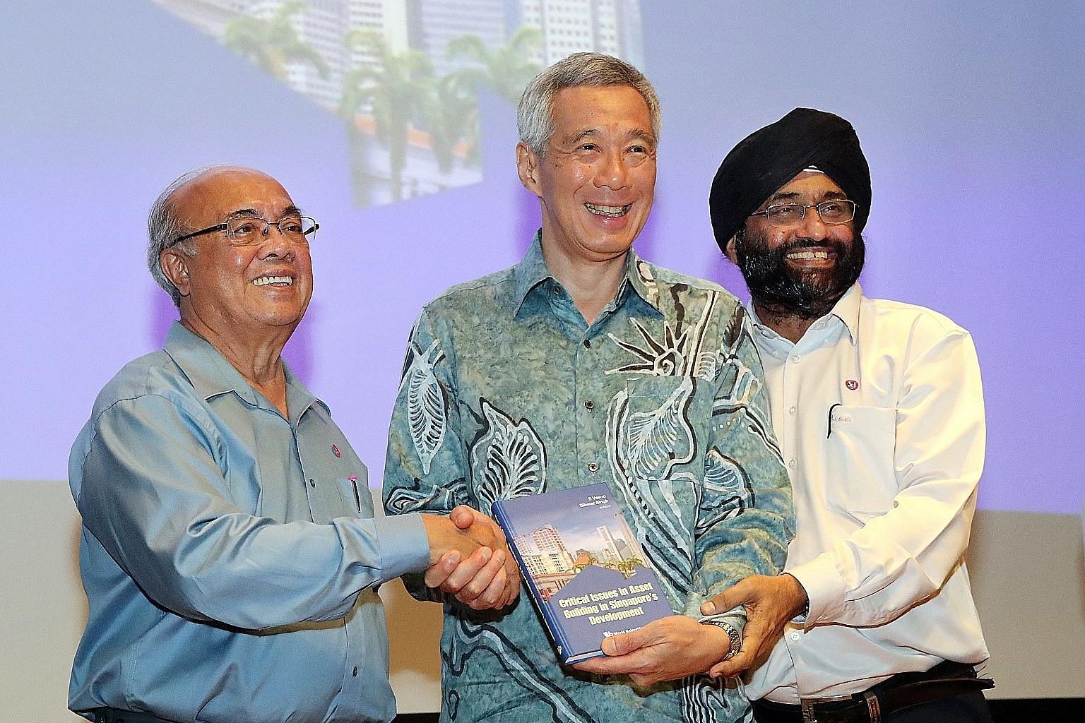 Prime Minister Lee Hsien Loong at the launch yesterday of a book edited by Associate Professor S. Vasoo (left) and Associate Professor Bilveer Singh. The book examines Singapore's asset-building policies through a series of essays, which look at trad