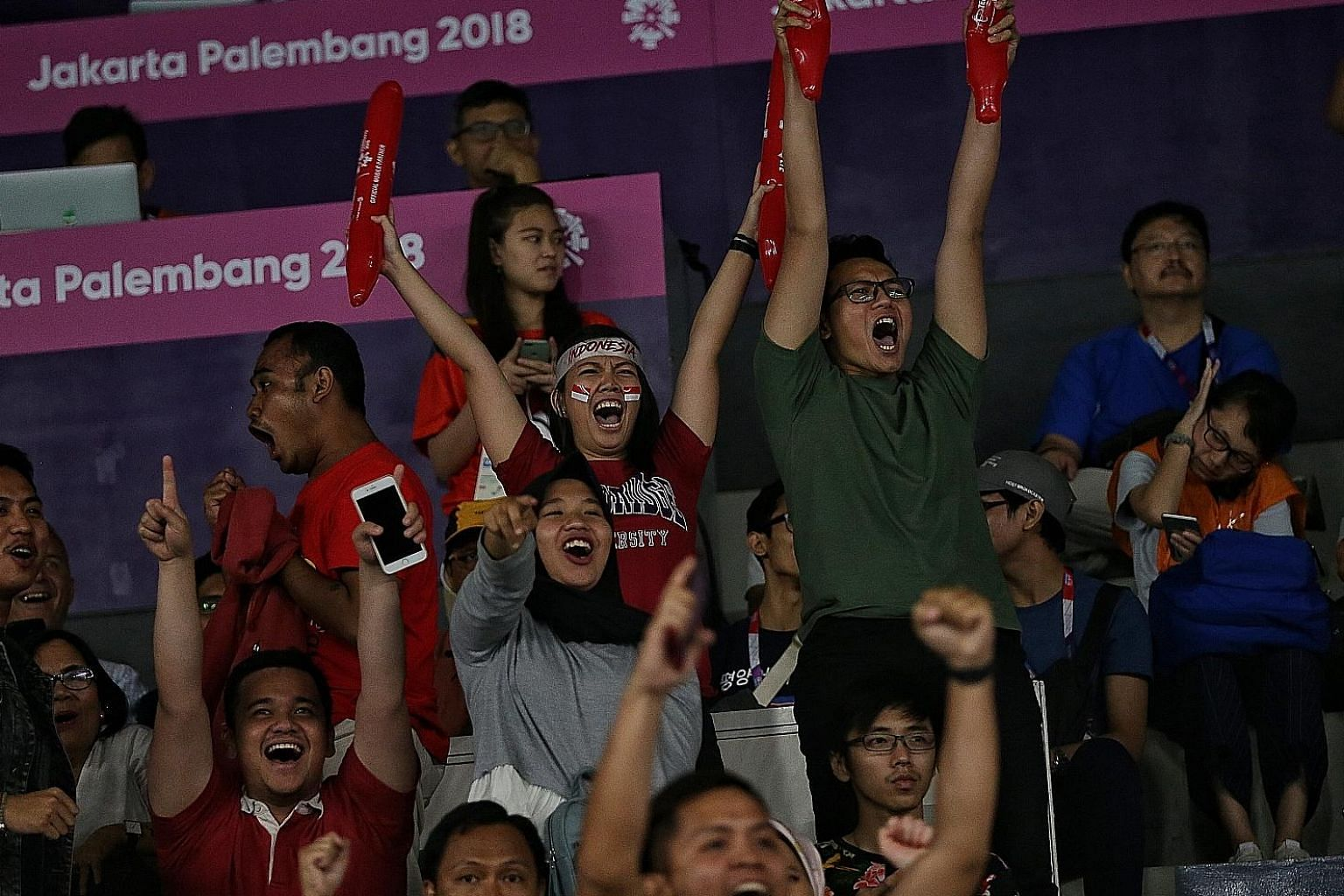 To say badminton is like a religion to Indonesians would not be an understatement. The home crowd was in full voice yesterday as supporters like Evangeline Launy (with Indonesia flag stickers on her cheeks) and Guntur Syayidu (in green) cheering thei