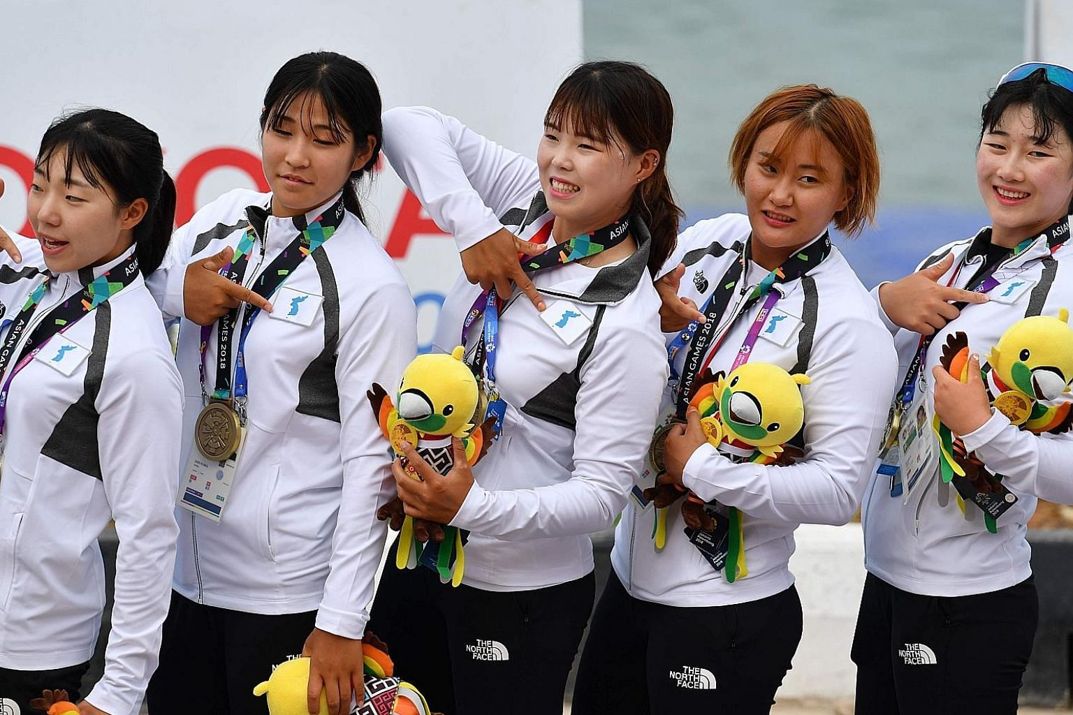 Members of the Unified Korea team pointing to the Korea Unification flag on their uniform, after receiving their bronzes during the medal ceremony for the women's 200m dragon boat final yesterday.