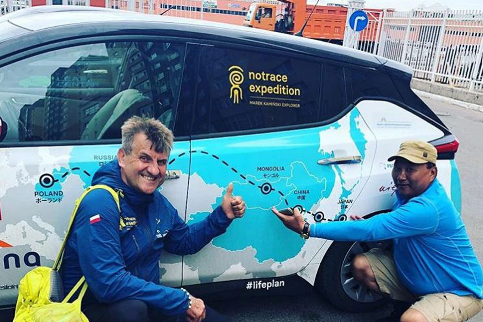 Mr Marek Kaminski with the Nissan Leaf vehicle he has been travelling in and a Mongolian he met during his drive. His stop in Japan marked the halfway point of his 32,000km No Trace Expedition.