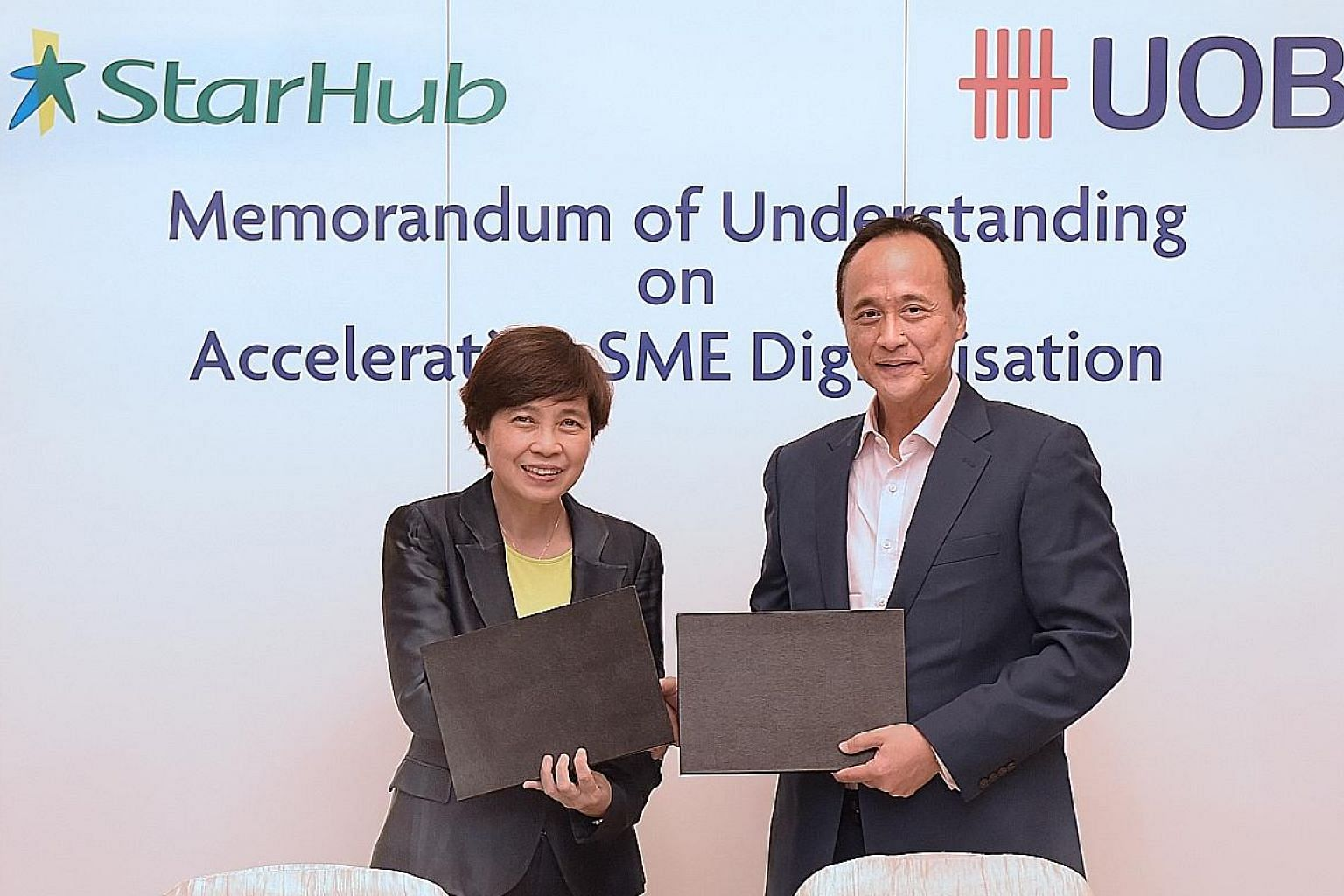 Dr Chong Yoke Sin, chief of StarHub's enterprise business group, and Mr Frederick Chin, head of group wholesale banking at UOB, at the signing of a memorandum of understanding earlier this month on their partnership to help SMEs here adopt digital bu